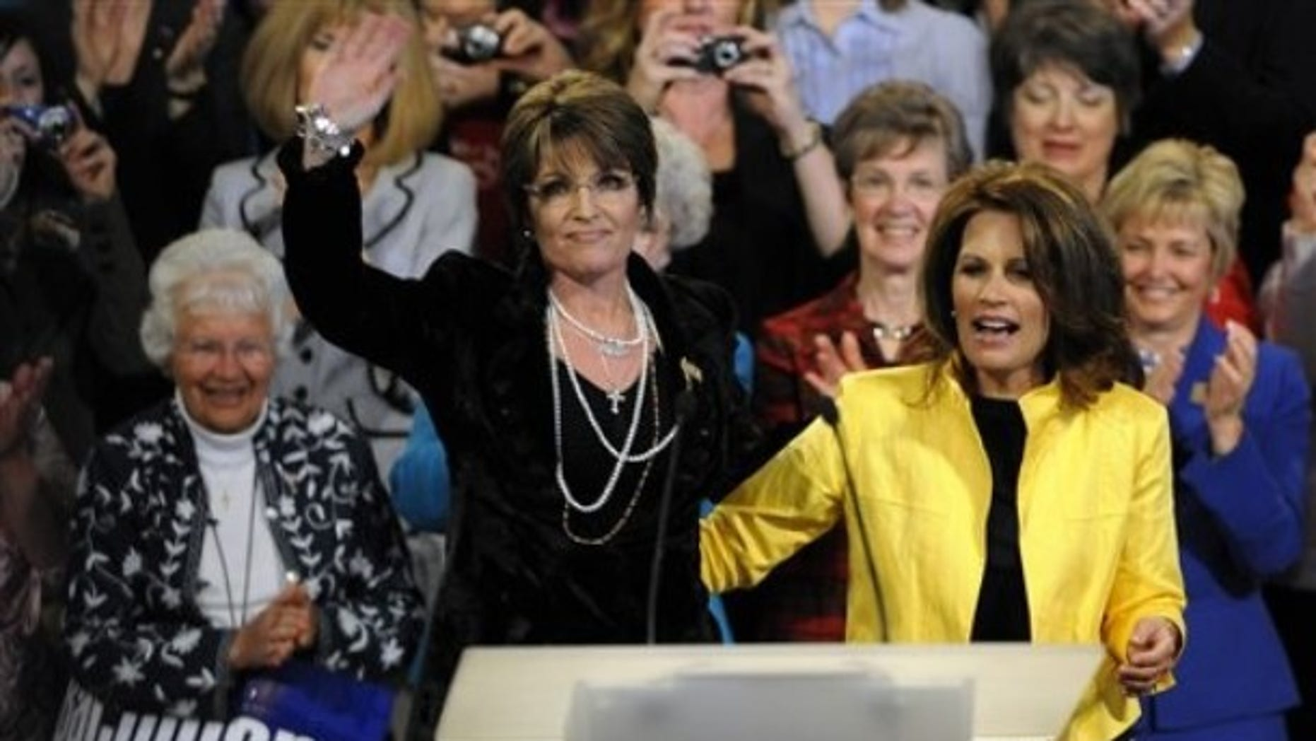 Wednesday: Sarah Palin, left, waves to the rally crowd after a campaign appearance for Rep. Michele Bachmann, R-Minn., in Minneapolis. (AP Photo)
