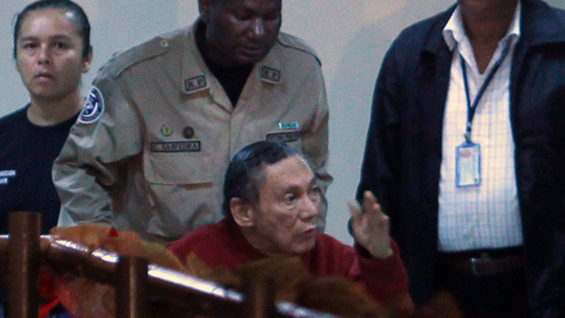 Dec. 11, 2011: Panama's former strongman Manuel Noriega gesturing while being carried in a wheelchair by a police officer inside El Renacer prison, on the outskirts of Panama City.