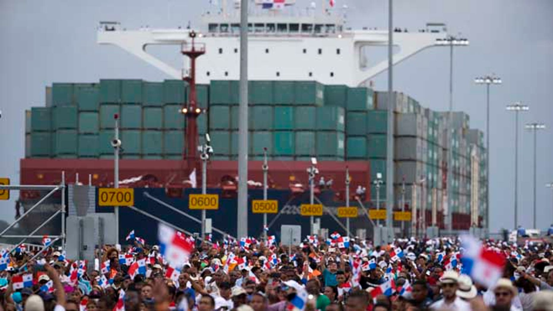 Thousands of spectators watch as the Neopanamax cargo ship, Cosco Shipping Panama, makes its way through the new Agua Clara locks, part of the Panama Canal expansion project, near the port city of Colon, Panama, Sunday June 26, 2016. The ship carrying more than 9,000 containers entered the newly expanded locks that will double the Panama Canal's capacity in a multibillion-dollar bet on a bright economic future despite tough times for international shipping. (AP Photo/Moises Castillo)
