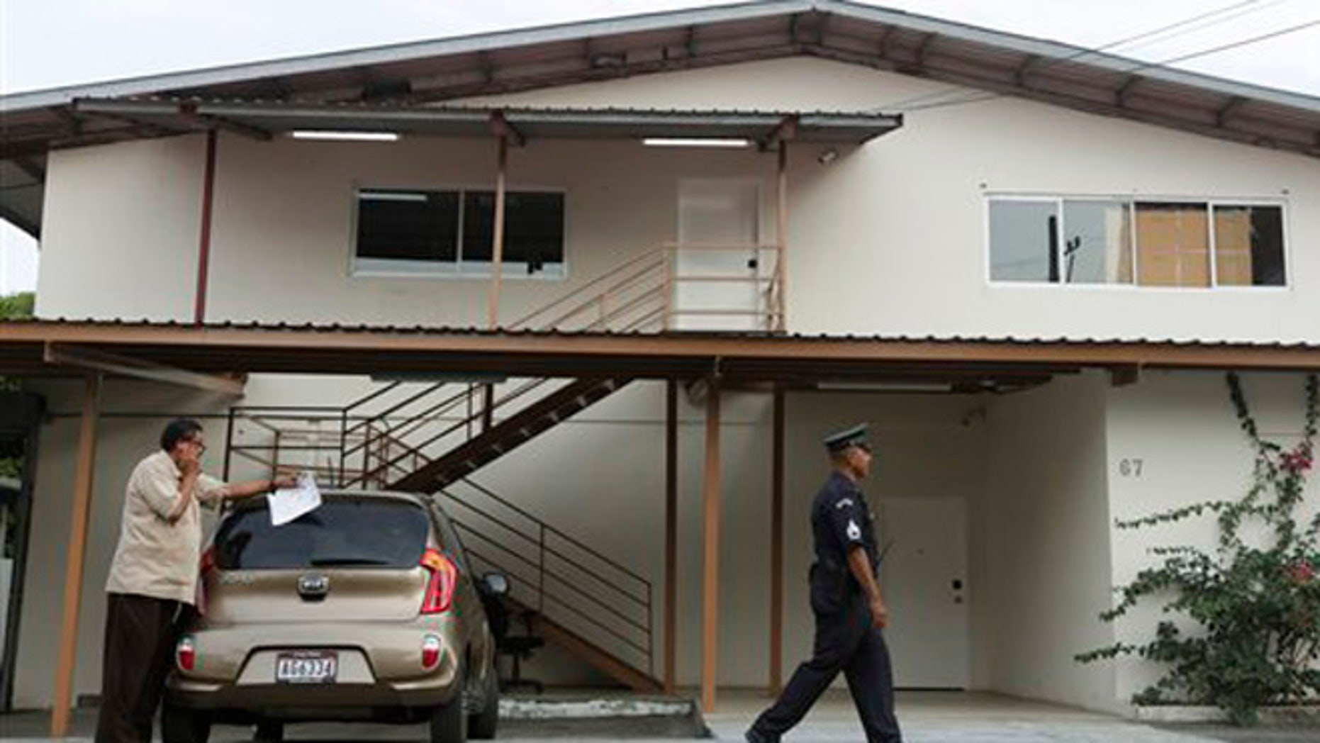 A Panamanian police officer and private security guard stand outside a warehouse used by the Mossack-Fonseca law firm, that was raided by prosecutors, in Panama City, Friday, April 22, 2016. A week before prosecutors had wrapped up their search of the Mossack Fonseca law firm looking for evidence of any illegal activity in the company at the center of a document leak that revealed details of offshore financial accounts.(AP Photo/Arnulfo Franco)