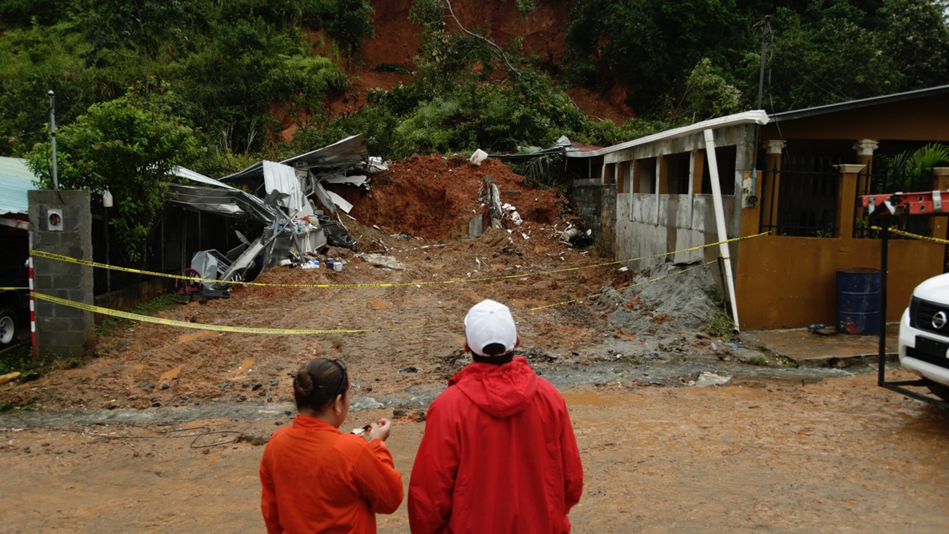 Civil Defense workers look the area where a couple was killed after their home was destroyed by a mudslide in Arraijan on the outskirts of Panama City, Tuesday, Nov. 22, 2016.
