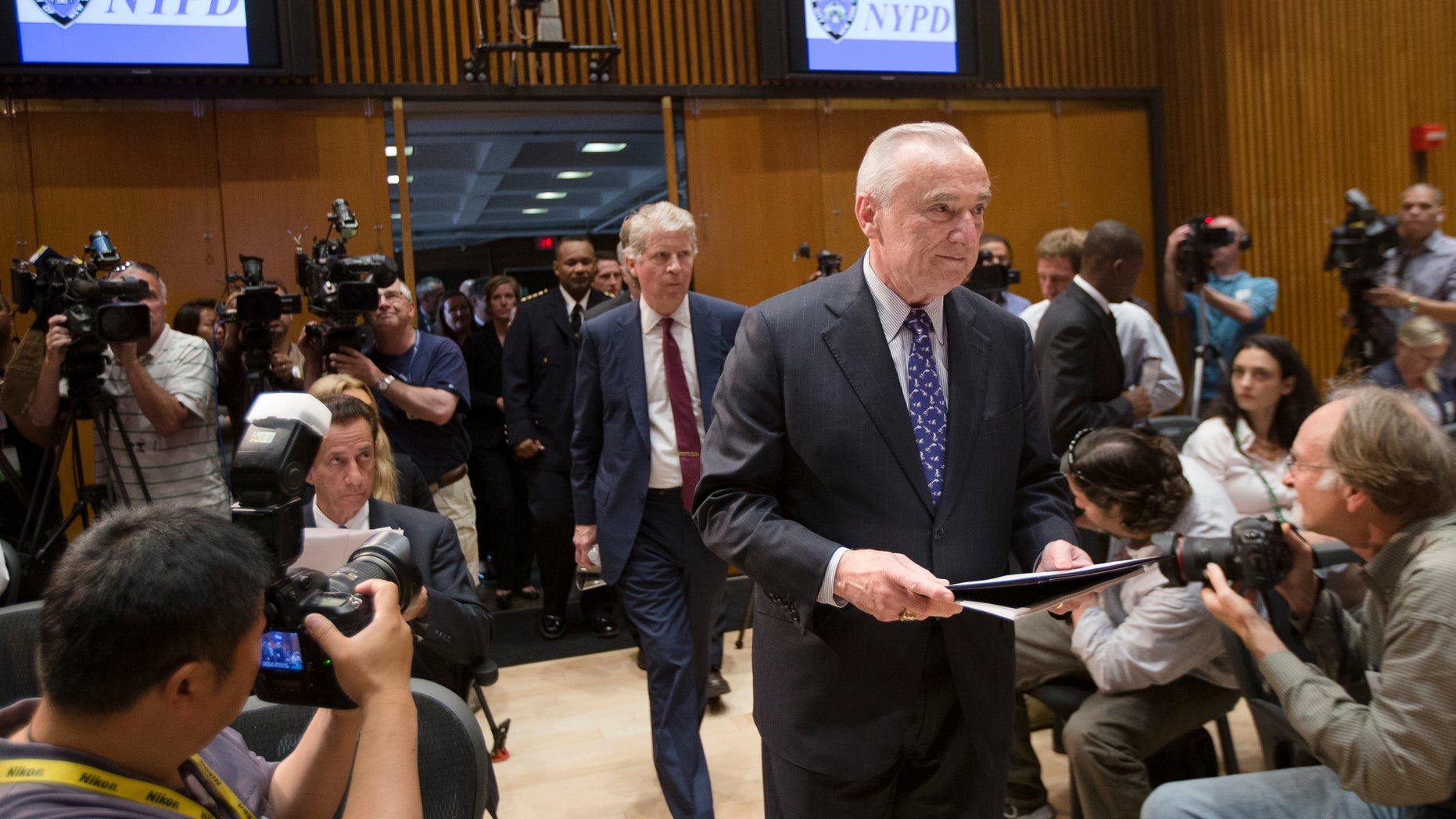 New York City police commissioner William Bratton enter a news conference Wednesday, June 4, 2014.