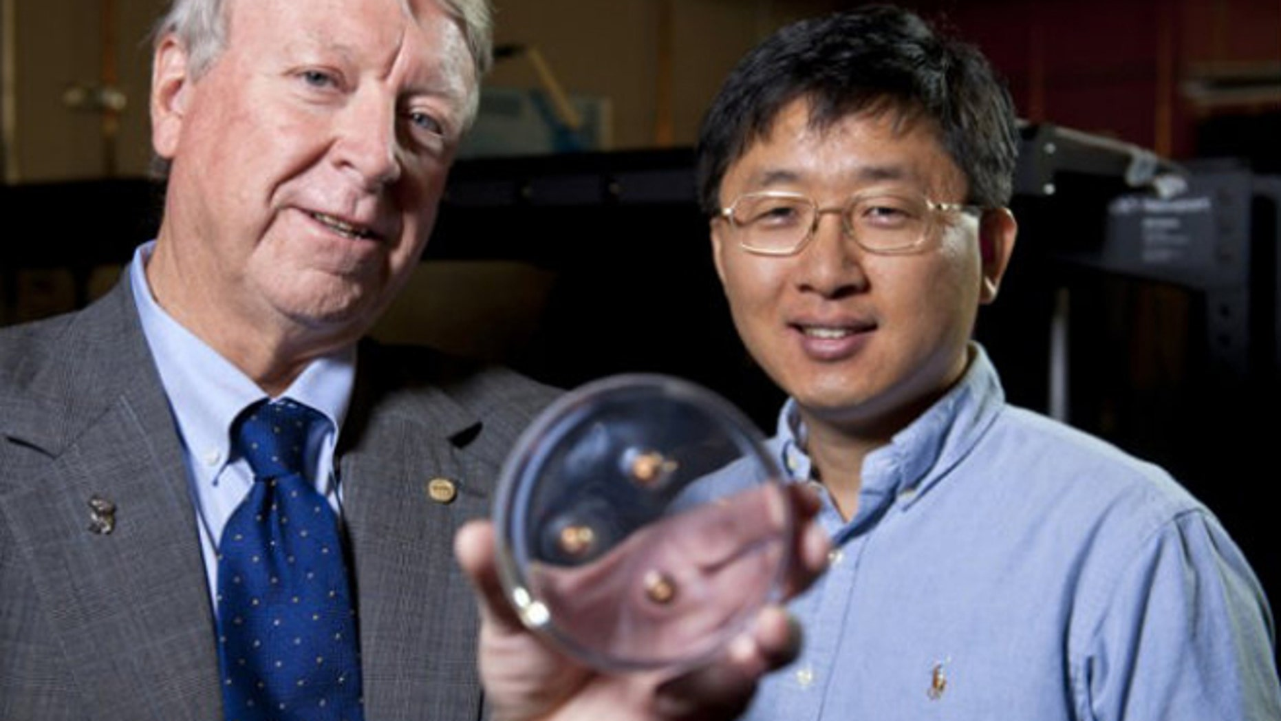 Rice University scientists Ned Thomas (left) and Jae-Hwang Lee with the material that stopped three bullets.