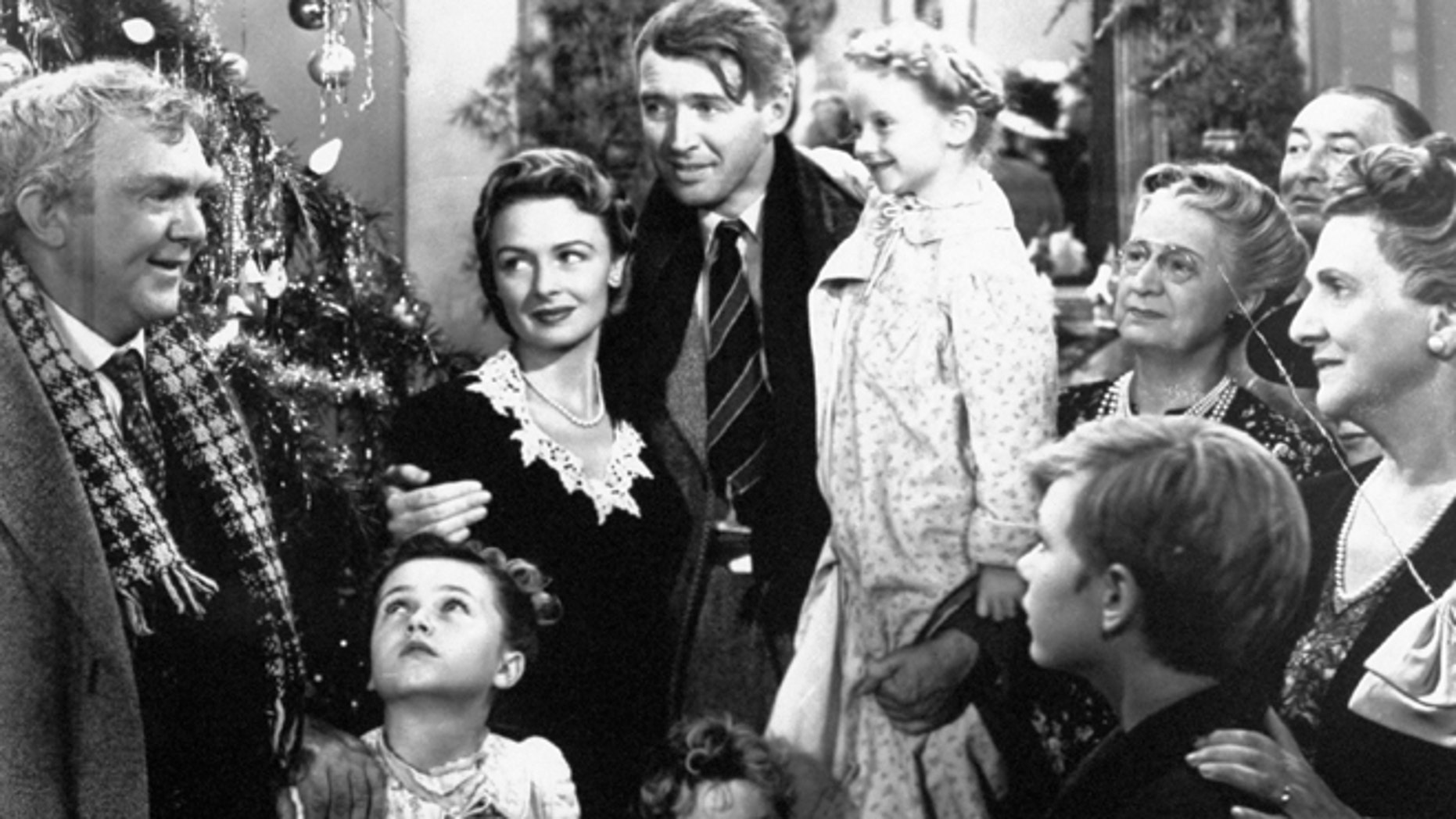 """In this 1946 file photo originally provided by RKO Pictures Inc., legendary actor James Stewart as George Bailey, center, is reunited with his wife played by actress Donna Reed, third from left, and family during the last scene of Frank Capra's """"It's A Wonderful Life."""""""