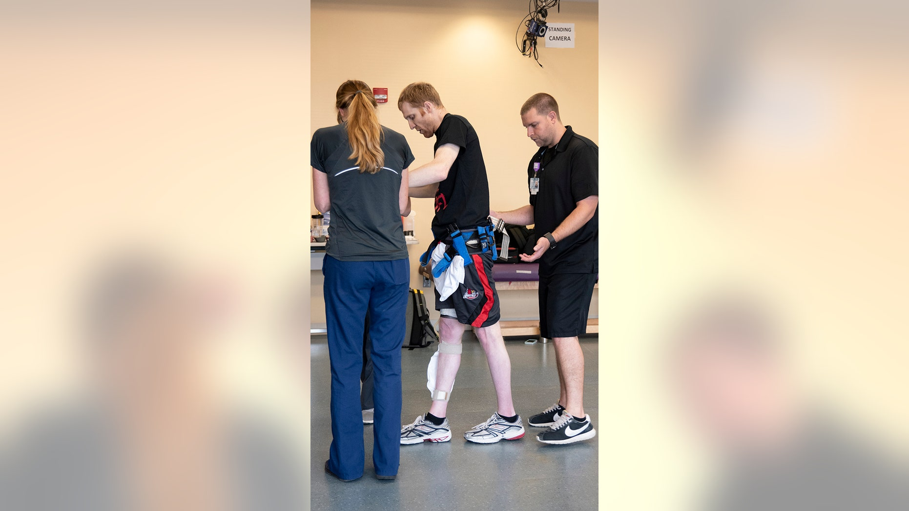 In this May 22, 2018 photo provided by the University of Louisville, Jeff Marquis of Louisville, Ky., is helped by a physical therapist during a study at the university that aimed to help the paralyzed stand and take steps with a combination of spinal stimulation and intense rehab. Marquis was paralyzed in a mountain biking accident. (Tom Fougerousse/University of Louisville via AP)