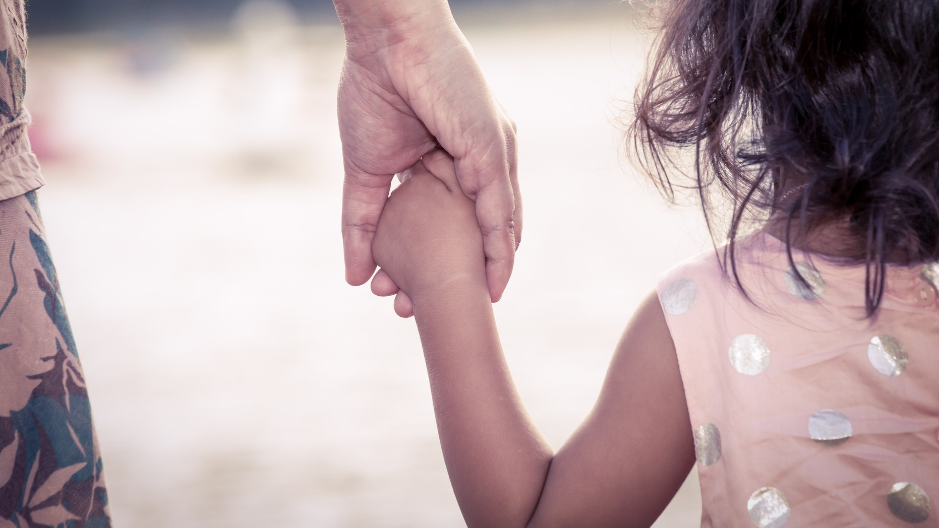 child cute little girl and mother holding hand together with love in vintage color filter