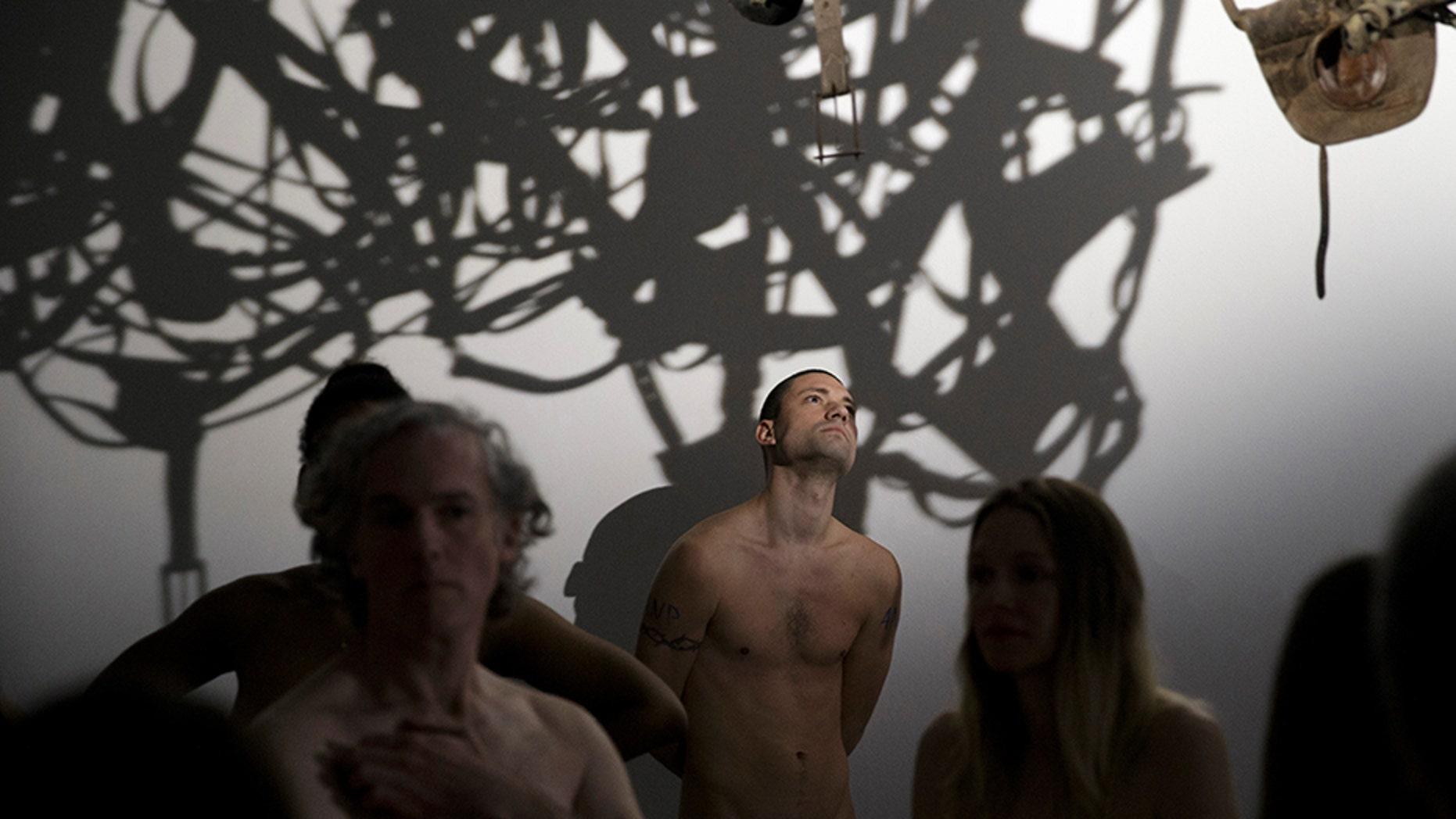 Members of the ANC (Association des Naturistes de Paris) taking part in a nude visit of the 'Discorde, Fille de la Nuit' season exhibition at the Palais de Tokyo contemporary art centre in Paris.