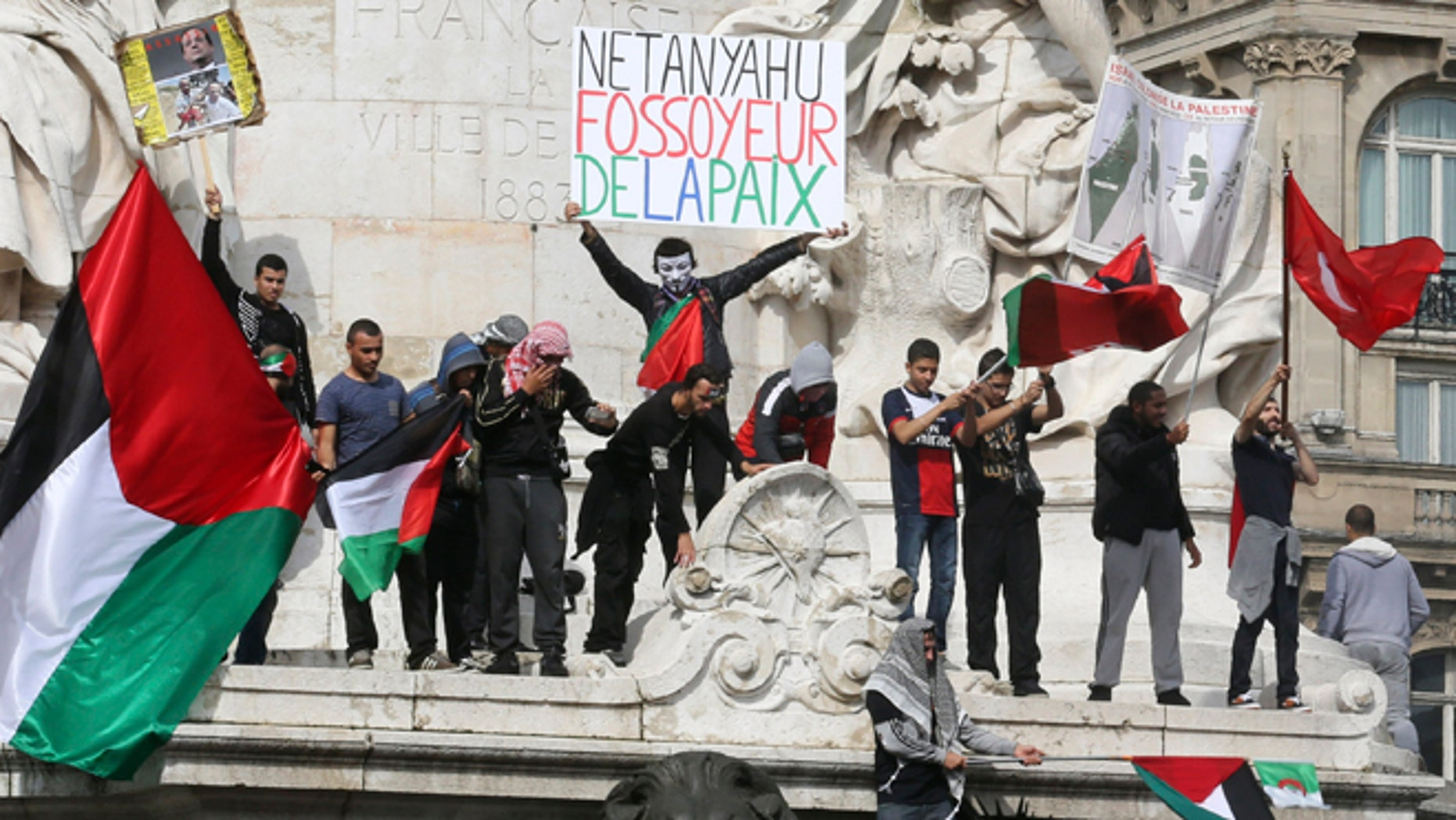 """July 13, 2014: Pro-Palestinian demonstrators wave Palestinian flags and chant anti Israeli slogans on the statue of Republic in Paris, to protest against the Israeli army's bombings in the Gaza strip. Banner reads: """"Netanyahu gravedigger of peace."""" About 10,000 pro-Palestinian protesters marched through eastern Paris on Sunday demanding an end to Israeli strikes on Gaza, and accusing Western leaders of not doing enough to stop them."""