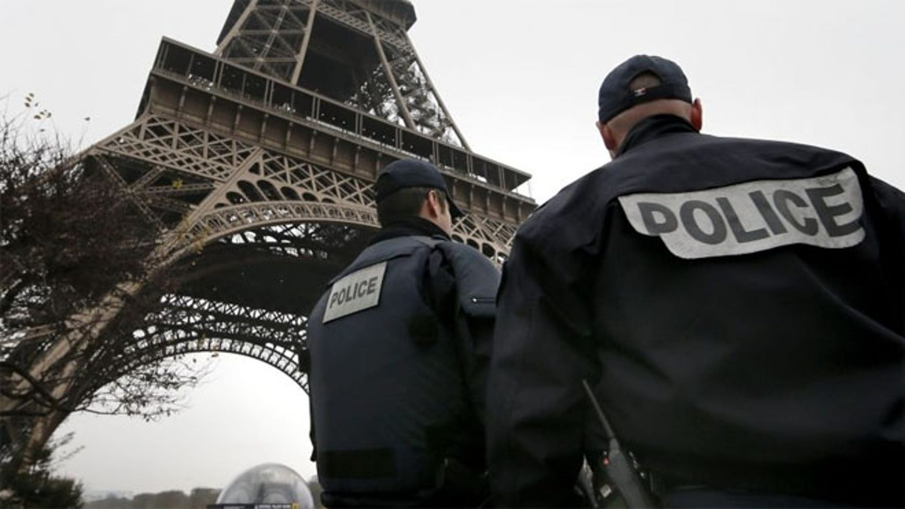 French police patrol near the Eiffel Tower in Paris after a shooting at the Paris offices of Charlie Hebdo.