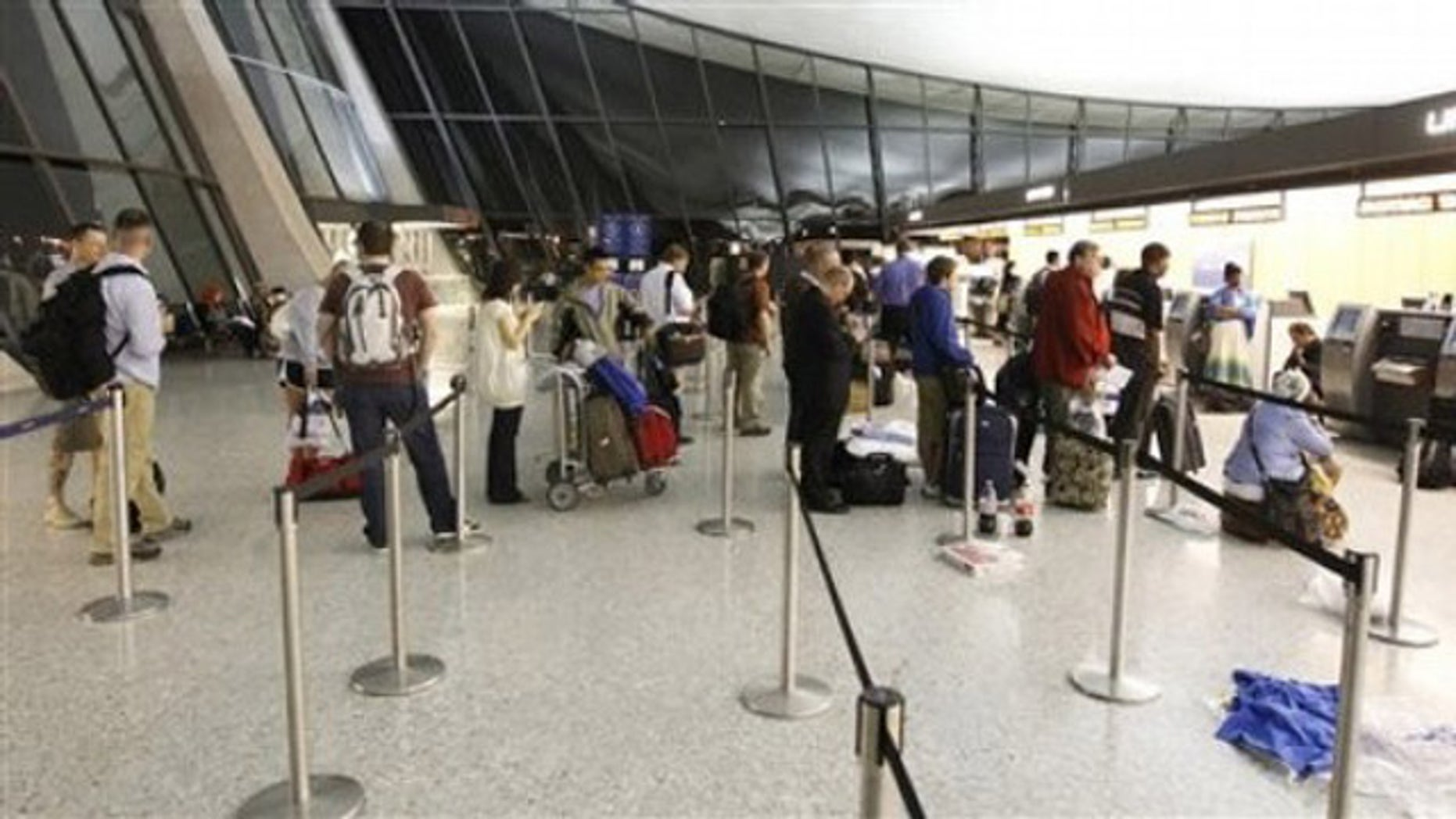 Airline passengers wait at the ticket counter of Washington Dulles International Airport in Chantilly, Va., June 18.