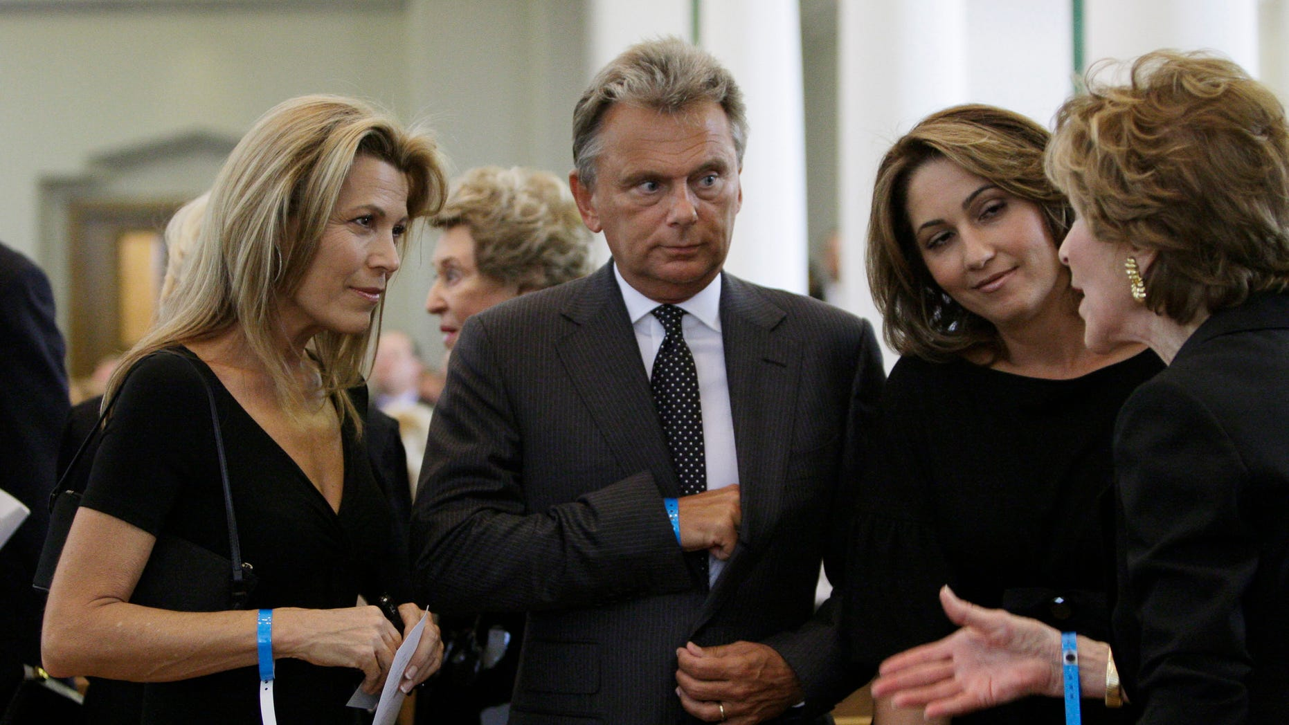 Vanna White (L) and Pat Sajak (C), television personalities from the 'Wheel of Fortune' game show created by Merv Griffin, and Sajak's wife Lesly Brown Sajak (2nd R) listen to an unidentified woman prior to funeral services for Griffin in Beverly Hills, California, August 17, 2007. Griffin died August 12, 2007 of prostate cancer at the age of 82. REUTERS/Kevork Djansezian/Pool  (UNITED STATES) - RTR1SVAK