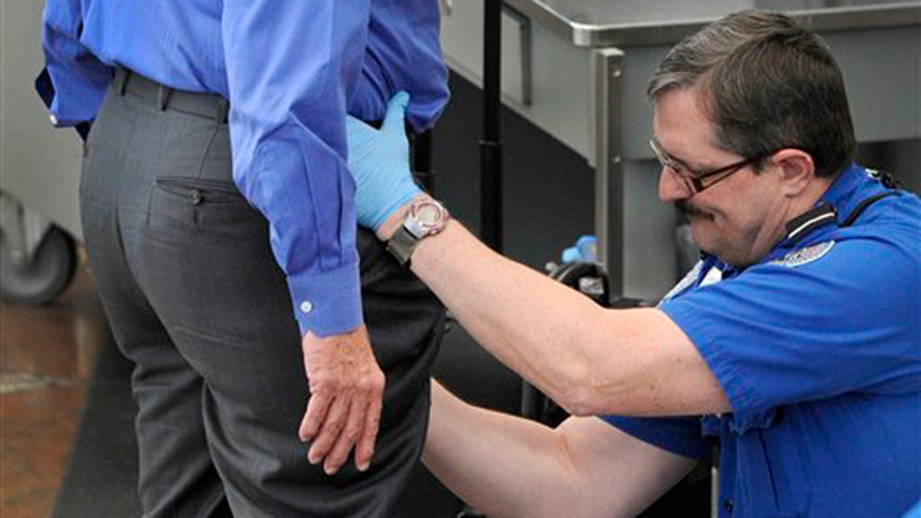 In this Nov. 17 photo, a Transportation Security Administration agent performs an enhanced pat-down on a traveler at Denver International Airport. (AP Photo)