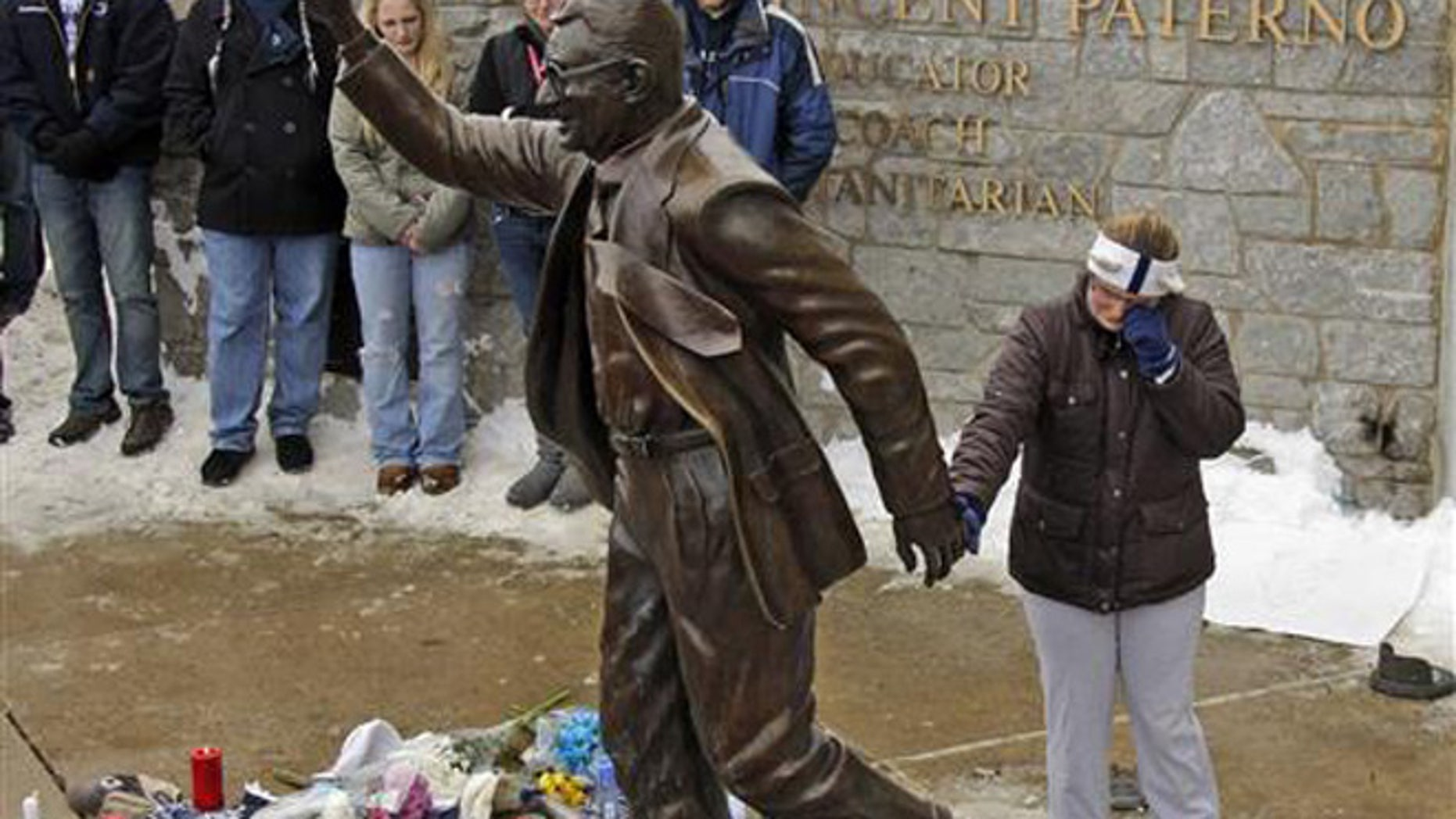 In this Jan. 22, 2012, file photo, a woman pays her respects at a statue of former Penn State football coach Joe Paterno outside Beaver Stadium on the Penn State University campus in State College, Pa.