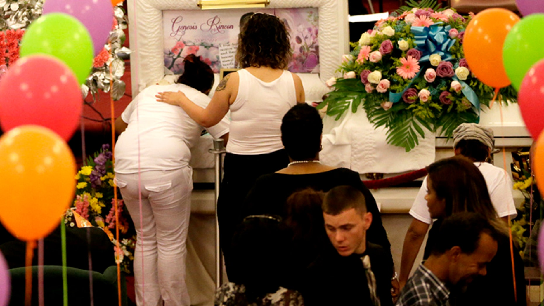 July 11, 2014: Jenny Calderon, left, is comforted by a woman as she leans into the casket containing the body of her daughter, Genesis Rincon, 12, who was hit by a stray bullet while riding a scooter, during the girl's funeral in Paterson, N.J.