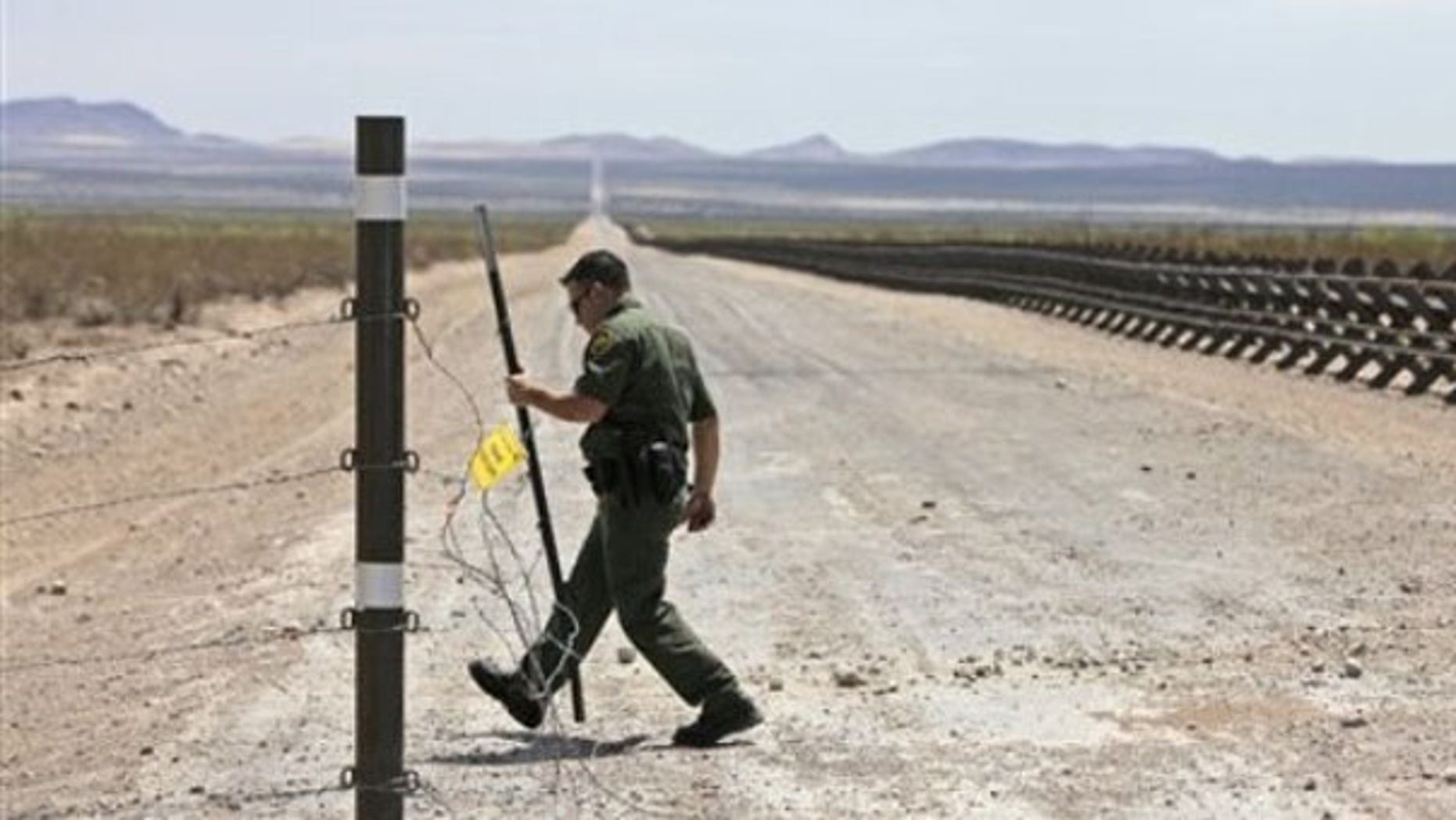 In this Aug. 6, 2009, photo, a U.S. Border Patrol agent opens a barbed wire fence leading to a road lined with vehicle barriers marking the U.S-Mexico border near Hermanas, N.M. (AP Photo)