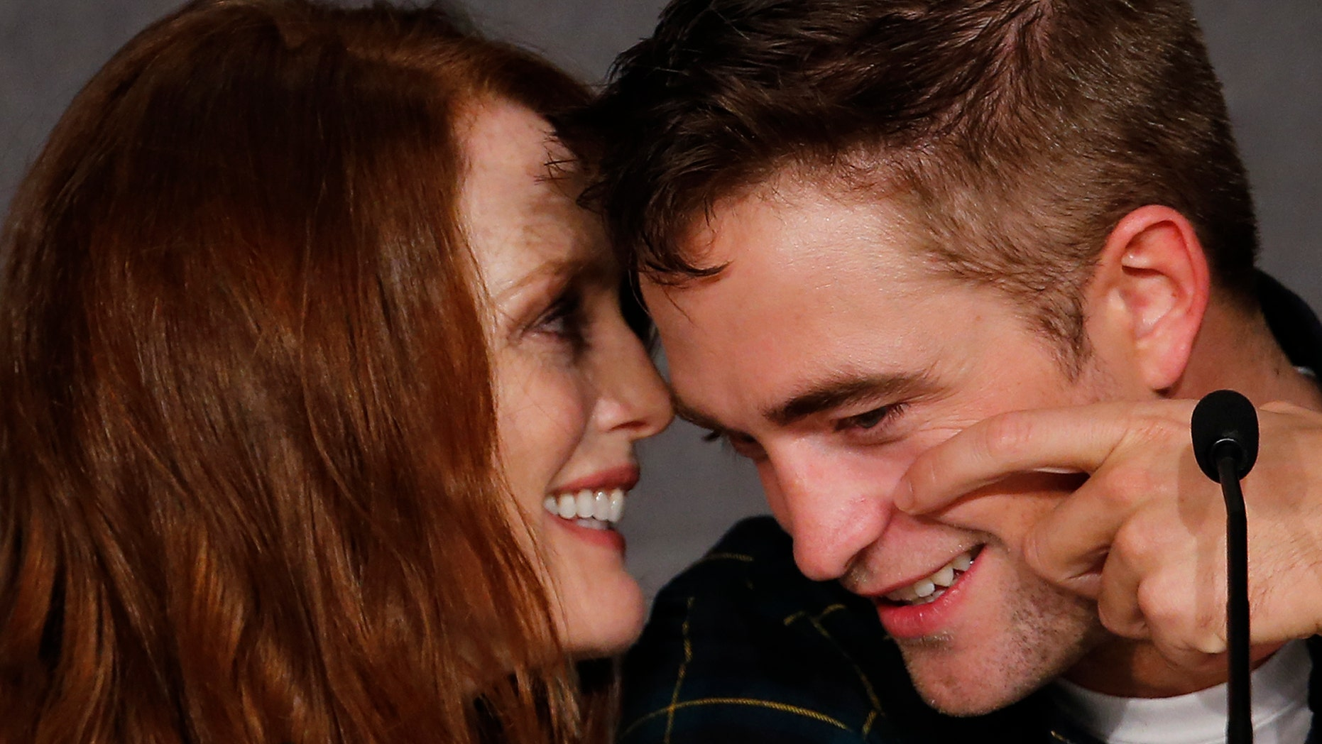 """May 19, 2014. Cast members Robert Pattinson (R) and Julianne Moore attend a news conference for the film """"Maps to the Stars"""" in competition at the 67th Cannes Film Festival in Cannes."""