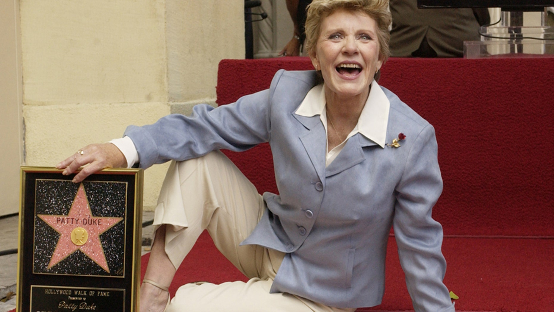 Award-winning actress Patty Duke poses for photographers following an unveiling ceremony, honoring her with the 2,260th star on the Hollywood Walk of Fame in Los Angeles, California August, 17, 2004.