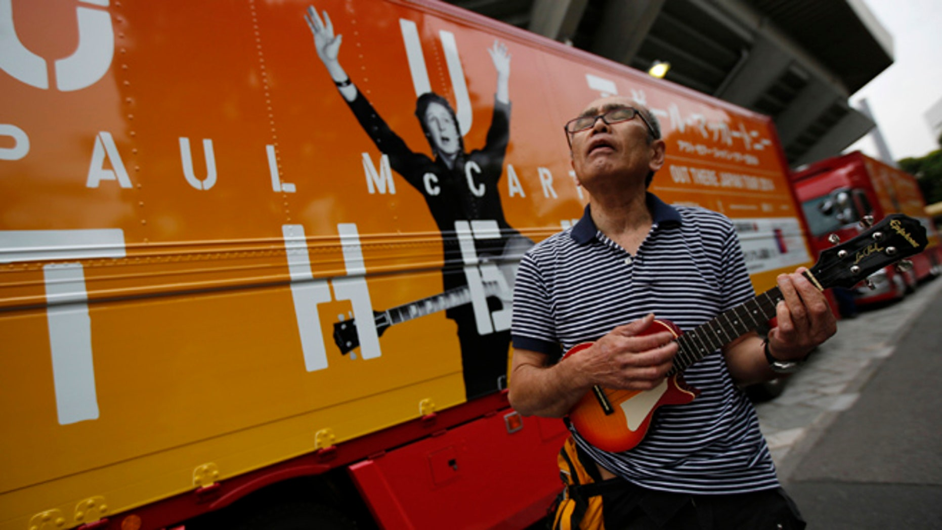 """May 20, 2014: Beatles fan Hitoshi Sekiguchi, 63, sings a Beatles song in front of a truck decorated with an advertisement for singer Paul McCartney's """"Out There"""" tour, after the cancellation of McCartney's concert at the Nippon Budokan in Tokyo."""