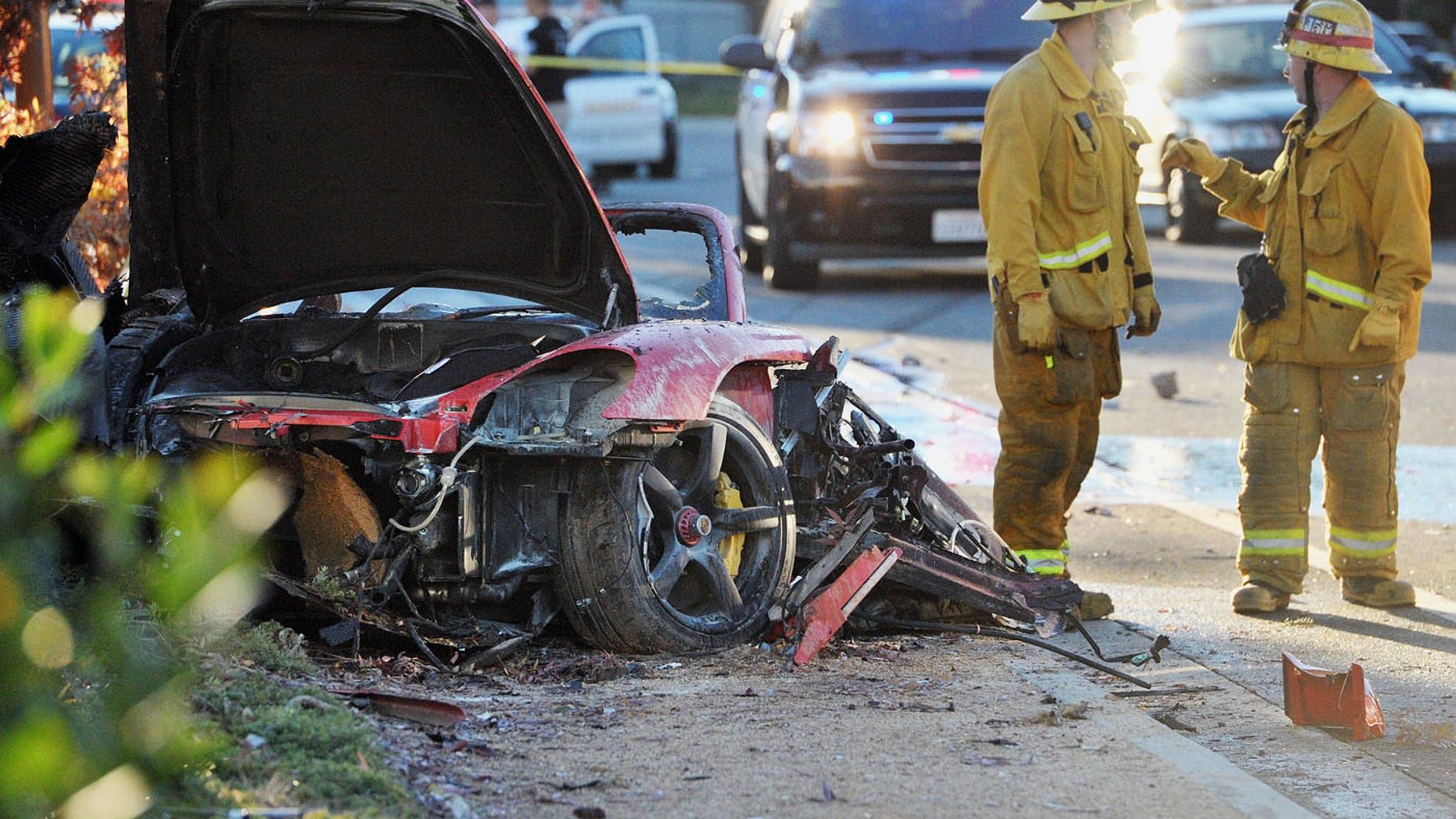 November 30, 2013. Sheriff''s deputies work near the wreckage of a Porsche that crashed into a light pole on Hercules Street near Kelly Johnson Parkway in Valencia, Calif.. A publicist for actor Paul Walker says the star  died in the crash north of Los Angeles.