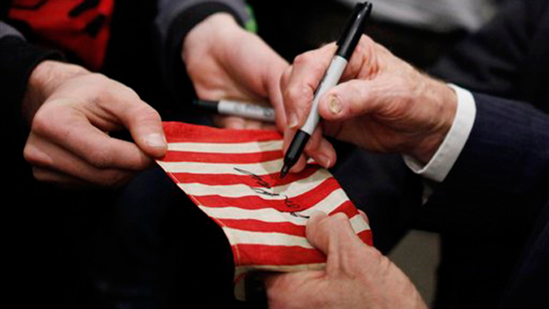 Dec. 29, 2011: Ron Paul signs a flag for a supporter as he campaigns in Council Bluffs, Iowa.