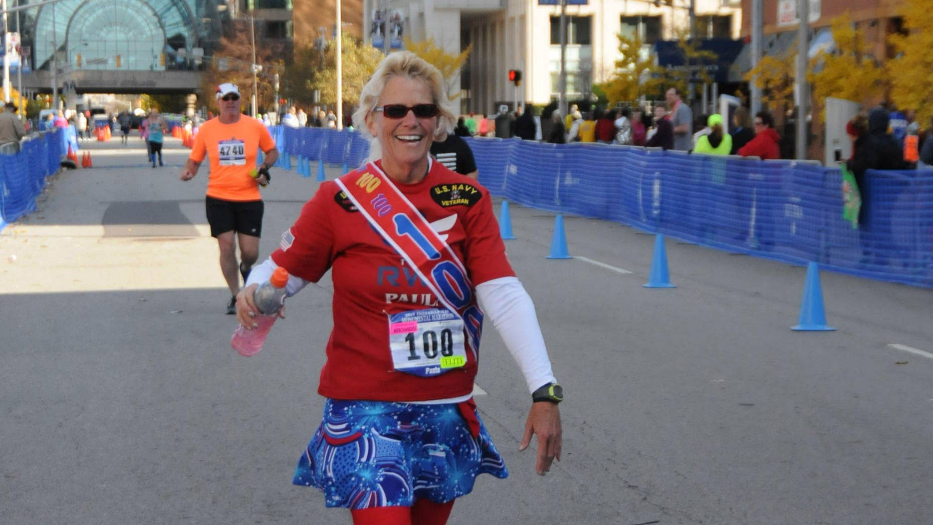 Paula Steinbach is recognized at the finish of the Monumental Marathon in Indianapolis, her 100th race at the distance.