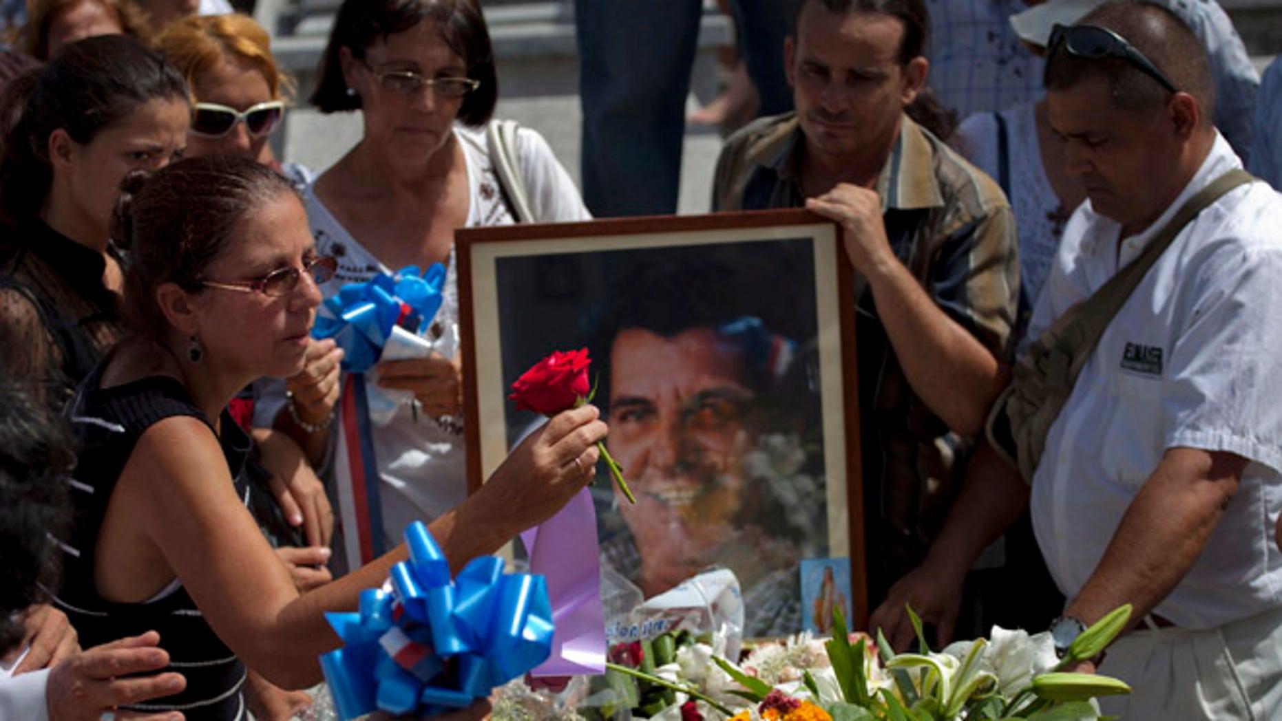 Ofelia Acevedo, viuda del difunto activista cubano Oswaldo Payá, coloca una flor sobre el ataúd durante el entierro en La Habana, martes 24 de julio de 2012. Payá, de 60 años, ganó fama internacional como promotor del Proyecto Varela, una campaña de firmas hace 10 años para pedir a las autoridades las libertades de expresión y reunión, entre otras. Fue considerada la iniciativa no violenta más grande para lograr cambios en el sistema cubano. Payá murió el 22 de julio de 2012 en un accidente automovilístico.  (AP Foto/Ramón Espinosa)