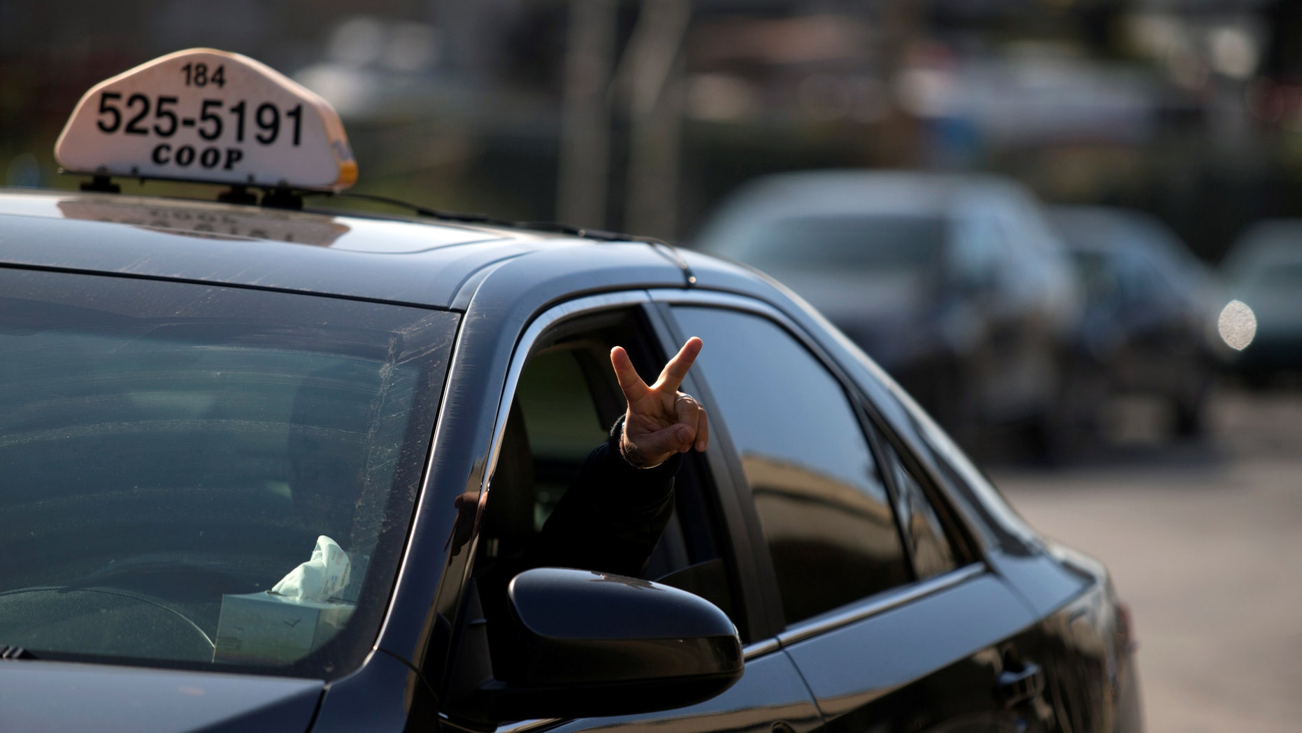 File photo - A taxi driver flashes a peace sign as he and other taxi drivers begin their protest against Uber in Montreal, Canada Oct. 5, 2016. (REUTERS/Christinne Muschi)