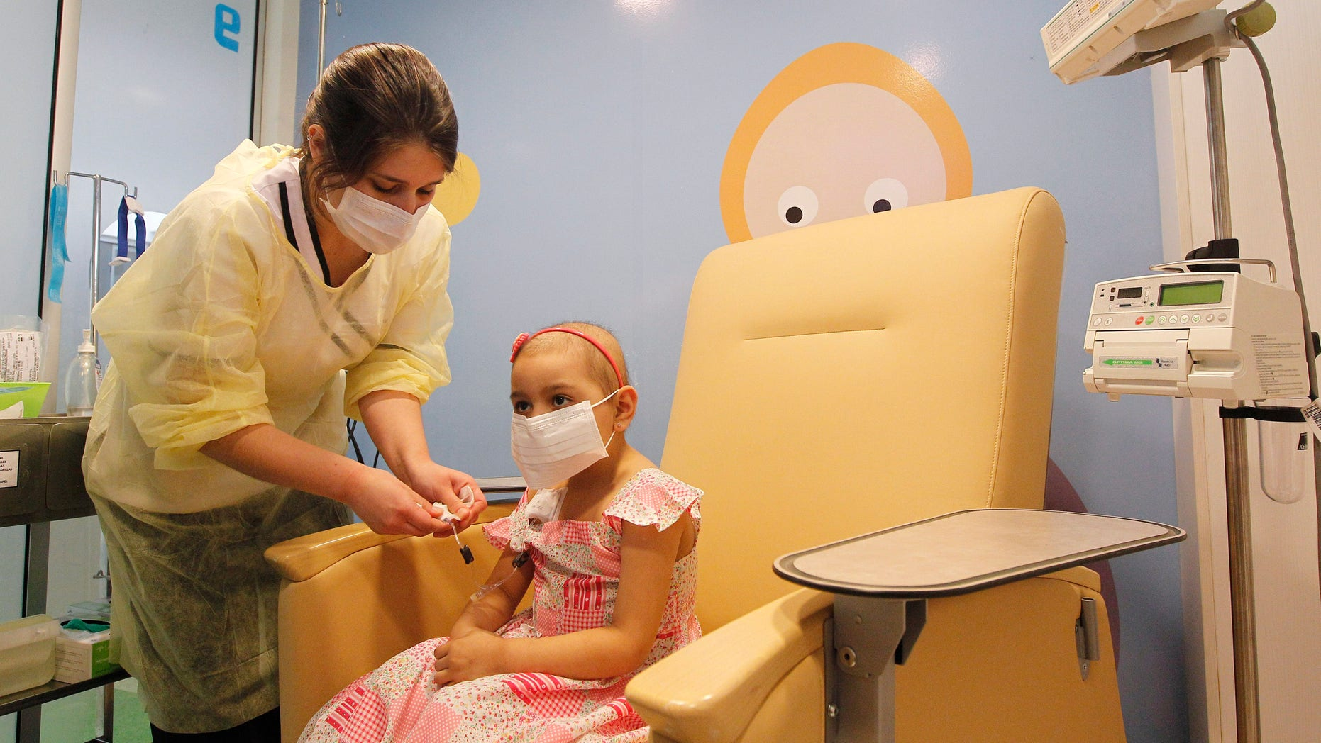 Alexandra Munoz, 5, who lost her hair due to chemotherapy to treat a malignant brain tumor, undergoes a session of treatment with the help of a nurse in the cancer ward of the Luis Calvo Mackenna Hospital in Santiago, October 20, 2014. REUTERS/Rodrigo Garrido