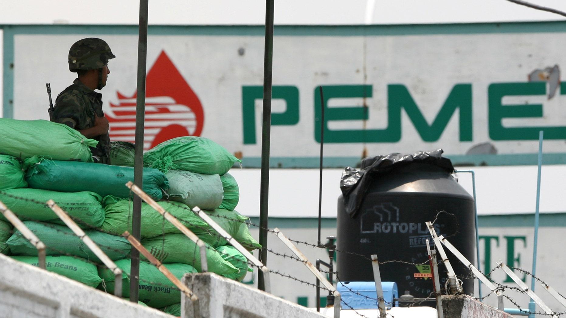 ARCHIVO - En esta foto de archivo del 11 de julio de 2007, un soldado del ejército mexicano monta guardia en una planta de la petrolera Pemex en la capital mexicana. El número de tomas ilegales en ductos de Petróleos Mexicanos se ha duplicado en lo que va de 2013, una de las pocas estadísticas relacionadas con delitos que, según el gobierno del presidente Enrique Peña Nieto, ha aumentado desde que asumió el cargo en diciembre pasado, dijo el gobierno el martes 23 de julio de 2013. (AP Foto/Eduardo Verdugo)