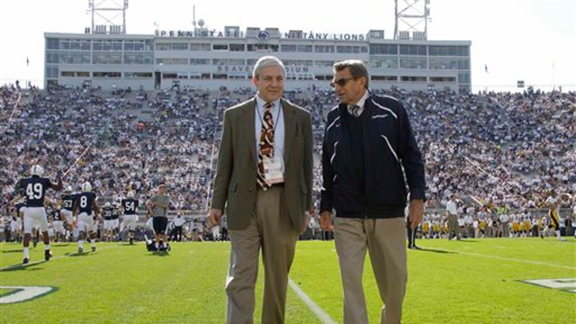 In this file photo, Penn State president Graham Spanier, left, and head football coach Joe Paterno chat before an NCAA college football game against Iowa in State College, Pa. (AP)
