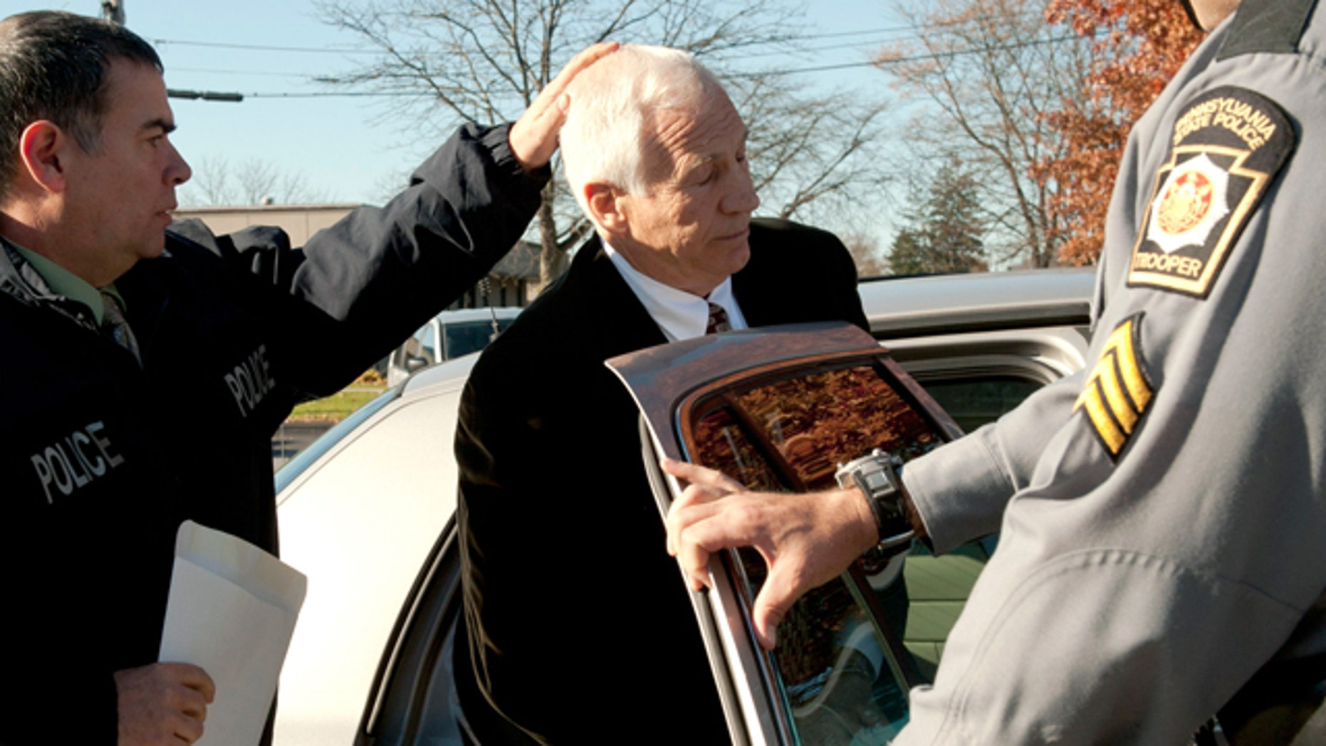 """Nov. 5, 2011: In this photo provided by the Pennsylvania Office of Attorney General, former Penn State football defensive coordinator Gerald """"Jerry"""" Sandusky, center, is placed in a police car in Bellefonte, Pa. to be taken to the office of a Centre County Magisterial District judge."""