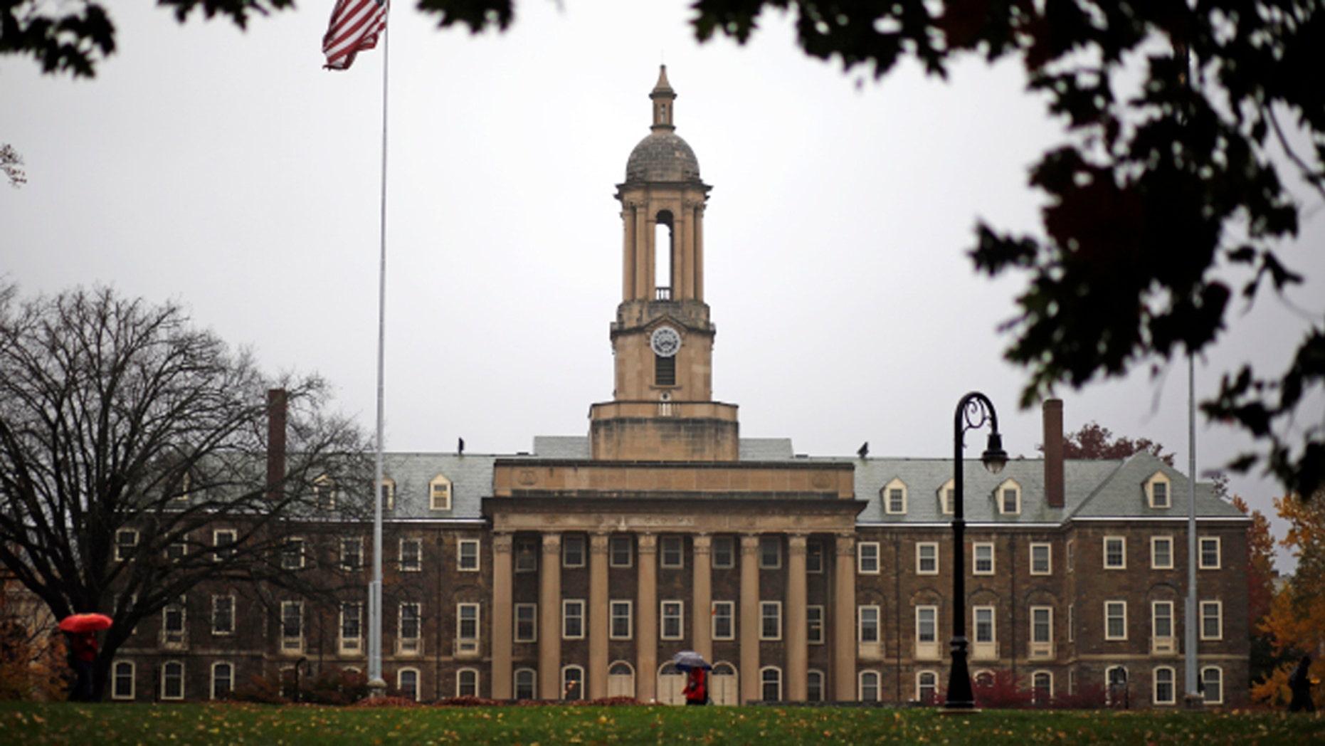 A Penn State student walks in the rain past Old Main on the Penn State main campus in State College, Pa., Wednesday, Oct. 28, 2015. (AP Photo/Gene J. Puskar)