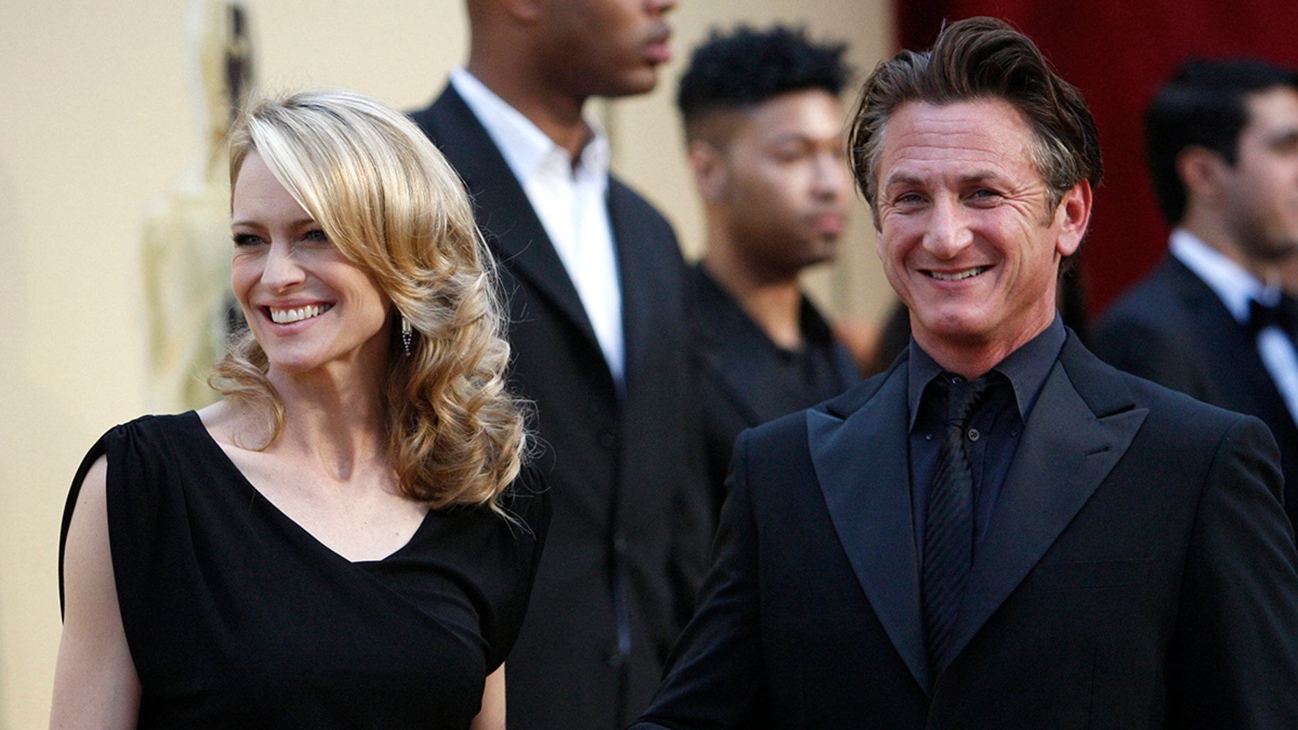 """Best actor nominee Sean Penn from the film """"Milk"""" and his wife Robin Wright Penn pause on the red carpet as they arrive at the 81st Academy Awards in Hollywood, California February 22, 2009. Sean Penn is dressed in Giorgio Armani and Robin Wright Penn, dressed in Monique Lhuillier. REUTERS/Mario Anzuoni   (UNITED STATES) (OSCARS-ARRIVALS) - GM1E52N0PKZ01"""