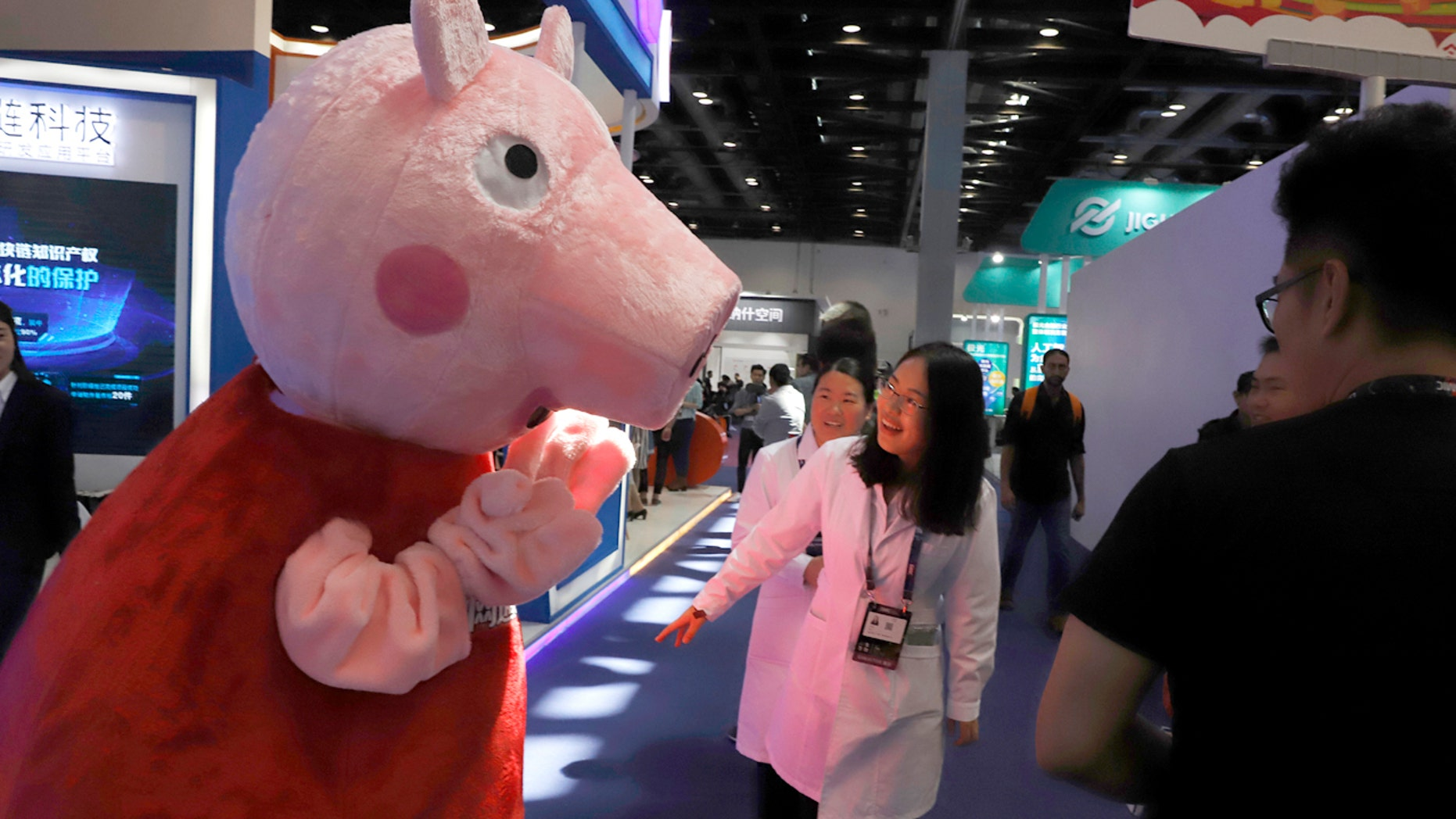 "In this April 27, 2018 photo, a woman reacts to a Peppa Pig mascot during the Global Mobile Internet Conference (GMIC) in Beijing, China. The cherubic British cartoon character, Peppa Pig, has become an unlikely target of China's censors as online fans use her porcine likeness in sardonic memes and ""gangster"" catchphrases. (AP Photo/Ng Han Guan)"
