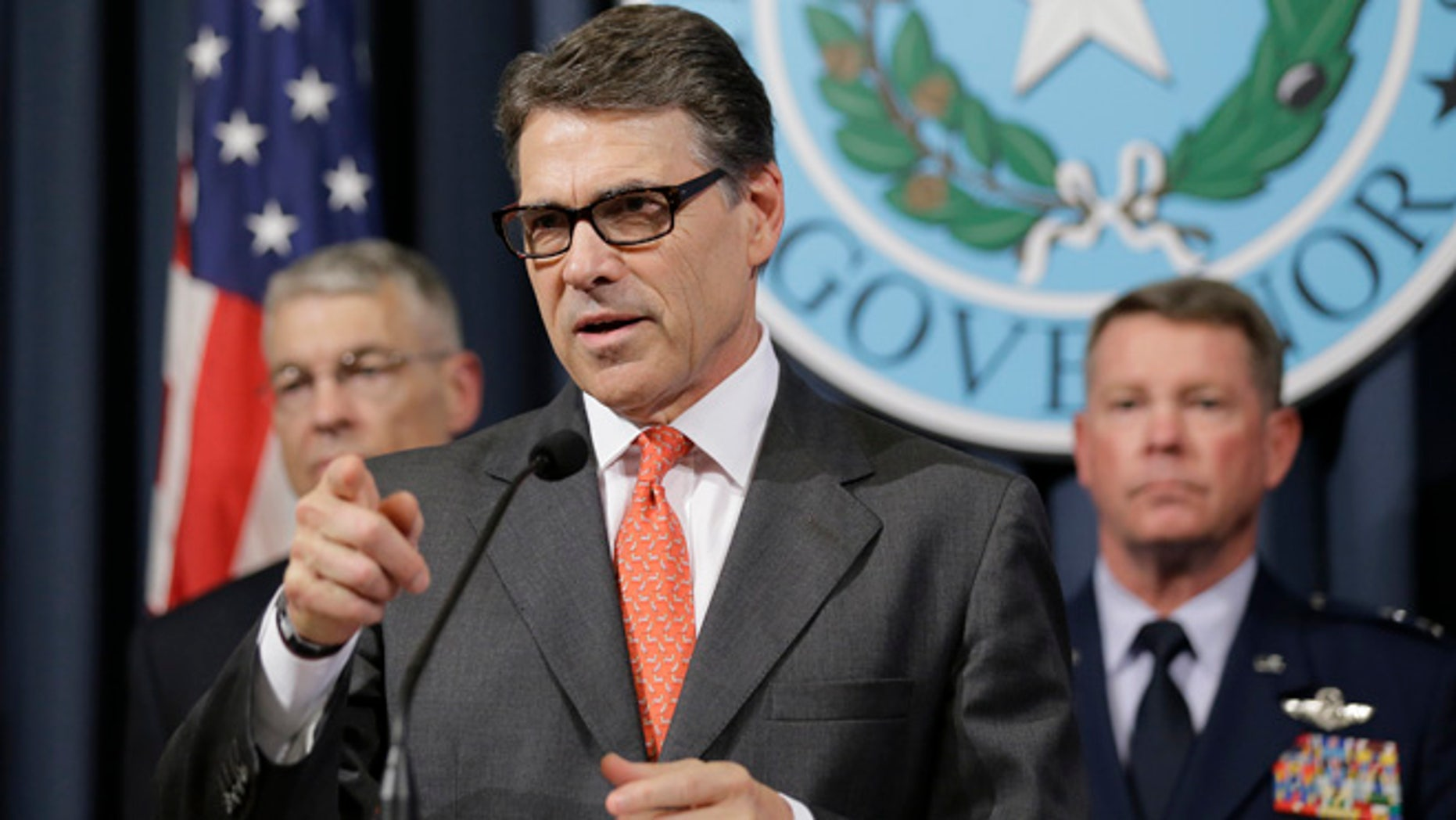 July 21, 2014: Gov. Rick Perry, center, speaks during a news conference in the Governor's press room in Austin, Texas.