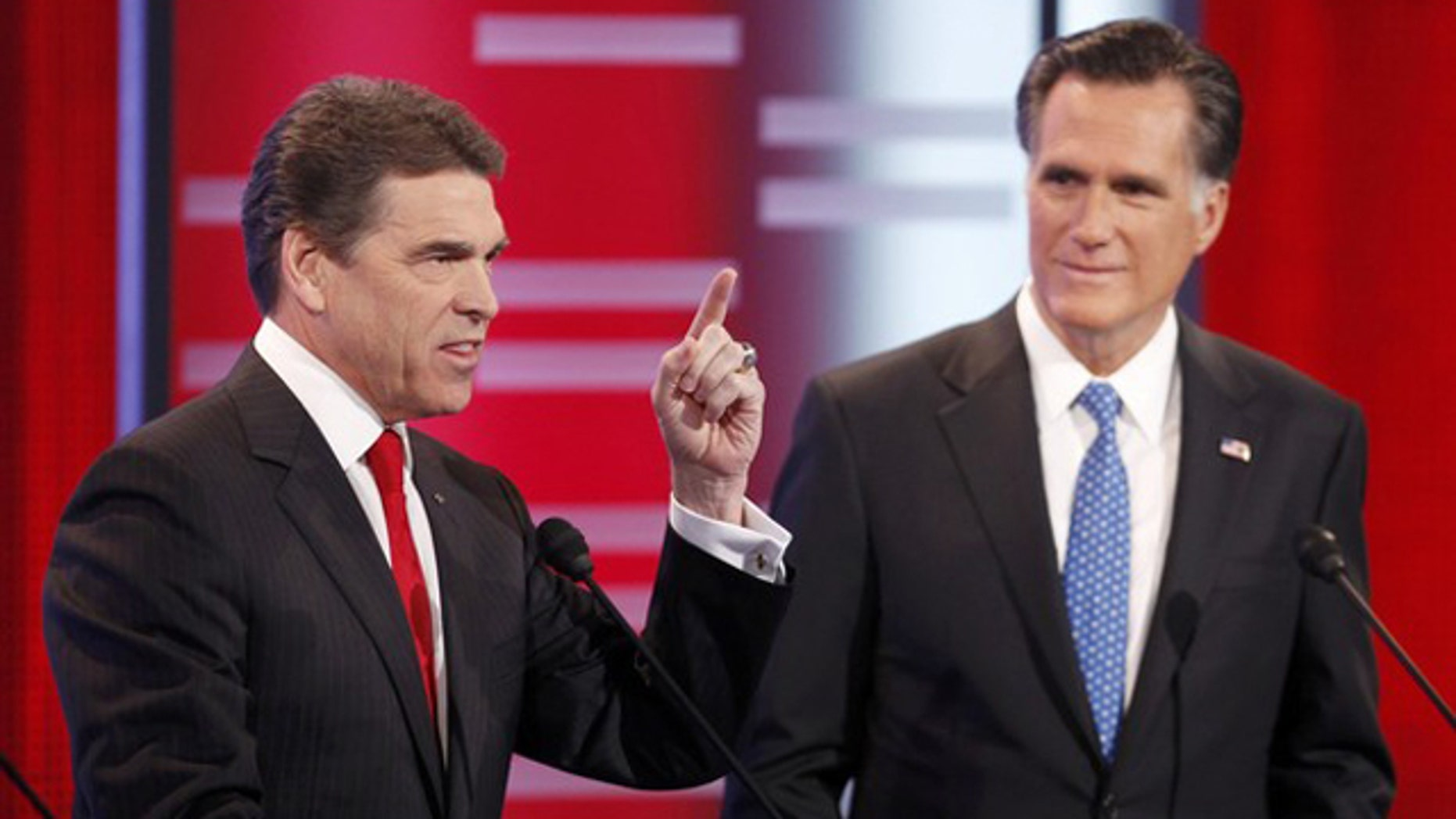 Dec. 10, 2011: Republican presidential candidate Texas Gov. Rick Perry makes a point as former Massachusetts Gov. Mitt Romney looks on during the Republican Party presidential candidates debate at Drake University in Des Moines, Iowa.