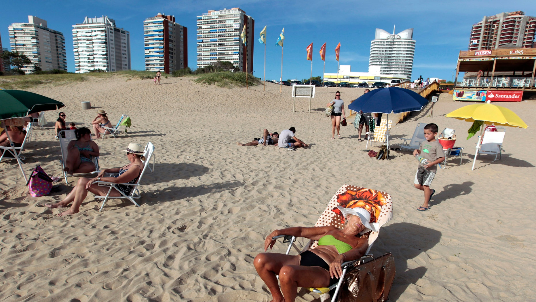 File photo: People sunbathe at the beach of the luxurious seaside resort of Punta del Este February 4, 2013. (REUTERS/Andres Stapff)