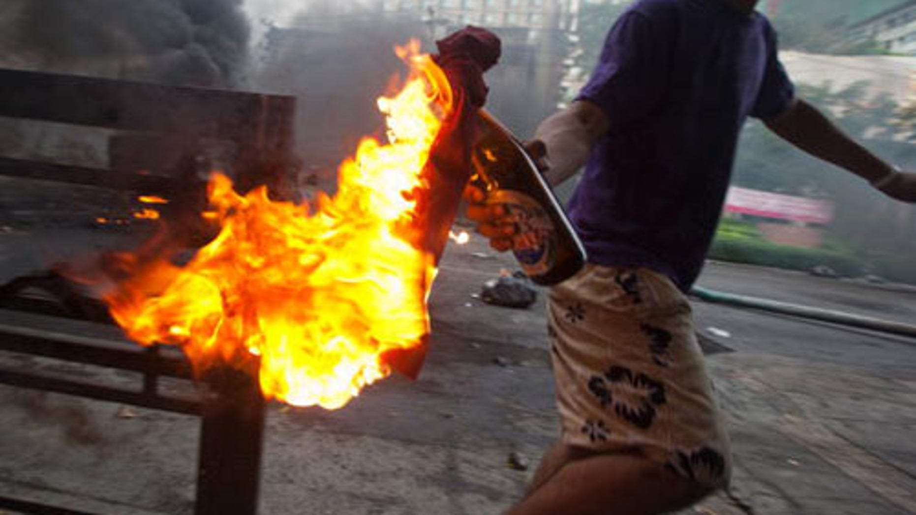 """BANGKOK, THAILAND - MAY 16:  An anti-government protester 'Red Shirt' throws a molotov cocktail toward Thai security forces as the violence in central Bangkok continues on May 16, 2010 in Bangkok, Thailand. So far at least 154 have been injured and over 20 killed in the clashes as the military and the government launched an operation to disperse anti-government protesters who have closed parts of the city for two months. A state of emergency is in effect that spreads to 17 provinces in the country. The Thai army declared certain protest areas where clashes are taking place as a """"Live Fire Zone.""""  (Photo by Athit Perawongmetha/Getty Images)"""