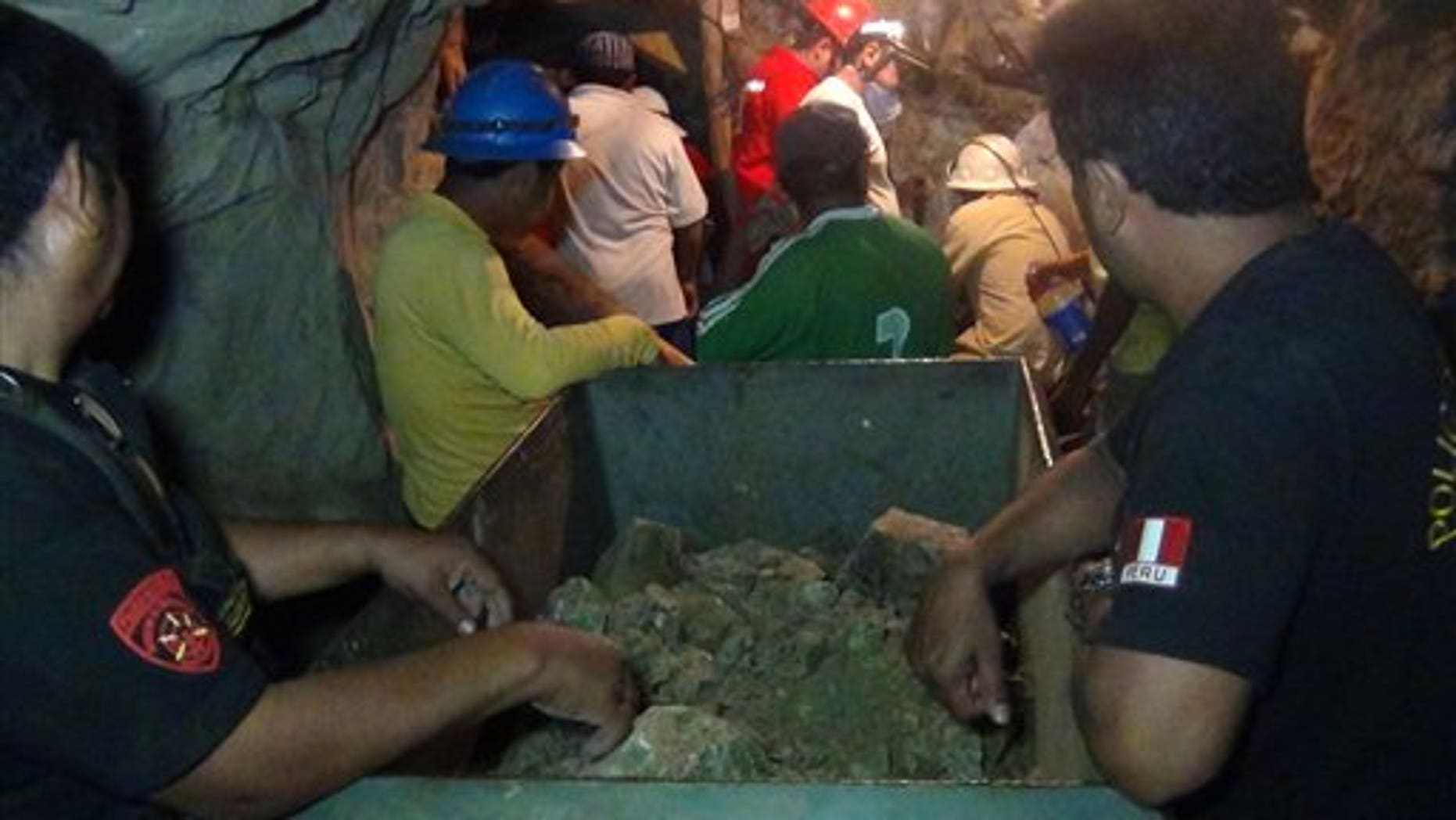 April 7, 2012: People work in a collapsed mine to rescue trapped miners in Ica, Peru. According to Peruvians authorities, nine miners trapped since Thursday in a collapsed mine are being supplied with sports drinks, soup and food while police, firefighters and other workers work to free them.