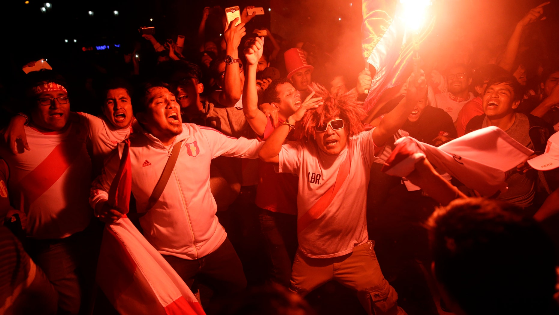 Fans celebrate after Peru qualified for the first time in 36 year for the soccer World Cup, in downtown Lima, Peru, Wednesday, Nov. 15, 2017. Peru defeated New Zealand 2-0 to win a two-leg playoff and earn the 32nd and last spot in the World Cup field in Russia. (AP Photo/Rodrigo Abd)