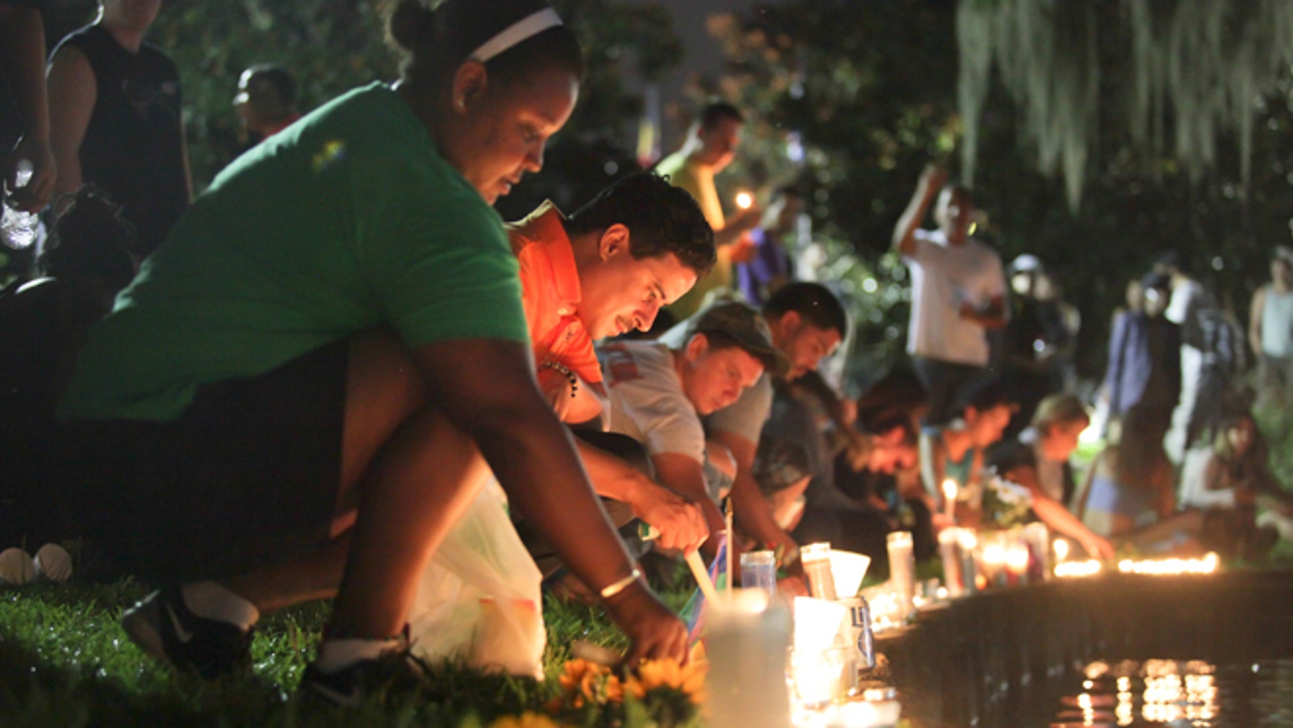 Wendy Frias, from left, and Hector Silva light candles along Lake Eola in Orlando, Sunday, June 12, 2016. The New York natives have made Orlando their home in recent years and came to the vigil for the victims of the Pulse night club tragedy.