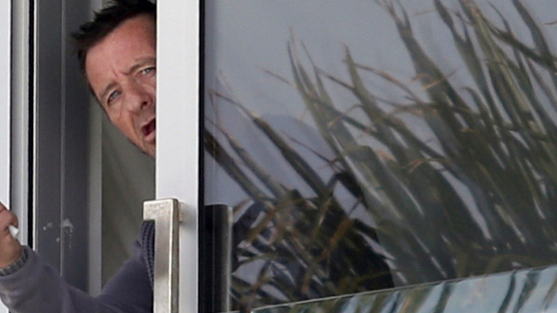 Nov. 6, 2014 file photo, Phil Rudd, drummer for the rock band AC/DC, gestures from a window at his house in Tauranga, New Zealand.