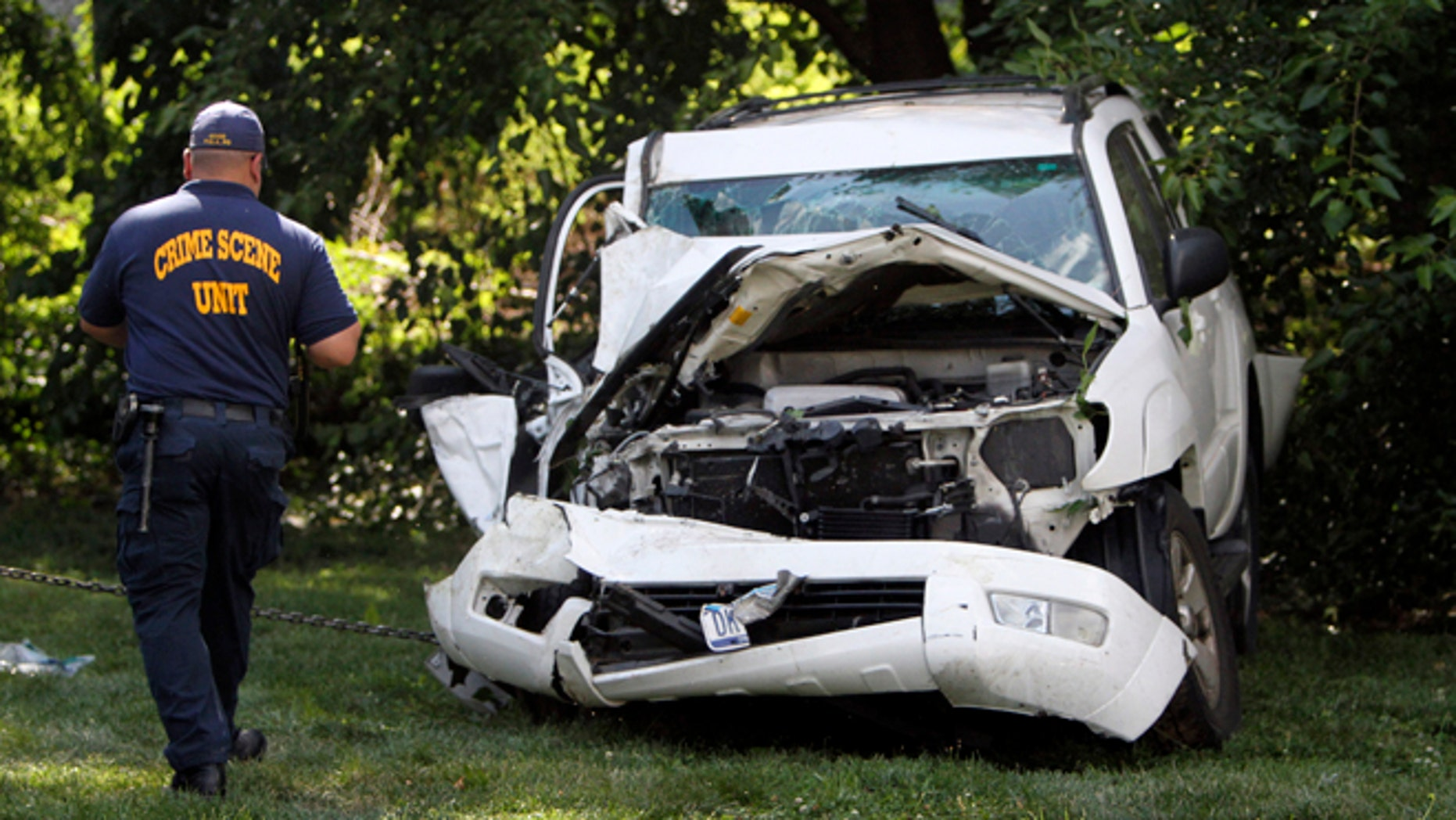 July 25, 2014: An investigator examines a heavily damaged SUV before it is towed from the scene of a fatal accident in North Philadelphia.