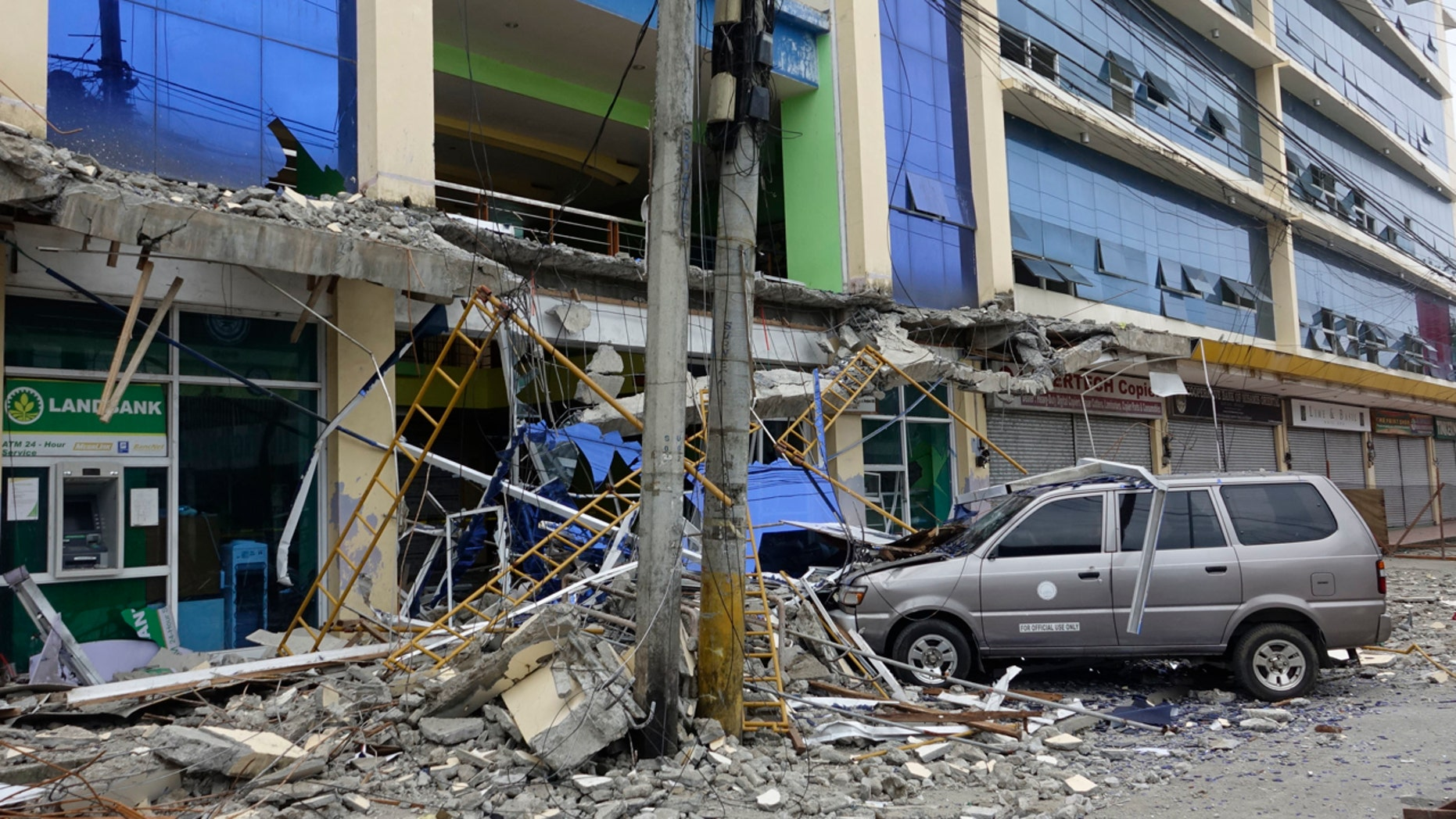 Fallen debris from a building are seen Saturday, Feb. 11, 2017 following a powerful nighttime earthquake that rocked Surigao city, Surigao del Norte province in southern Philippines.
