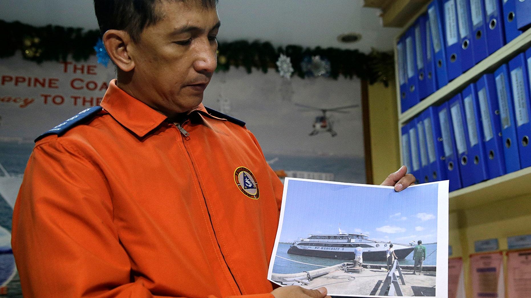 Coast guard spokesman Armand Balilo shows a file photo of the passenger vessel Mercraft 3 as he talks to reporters in Manila, Dec. 21, 2017.