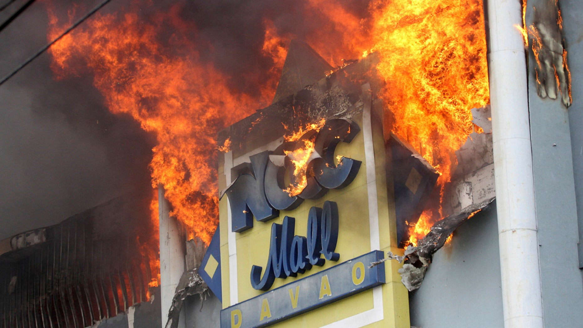 A fire rages on at a shopping mall Saturday, Dec. 23, 2017, Davao city, southern Philippines.