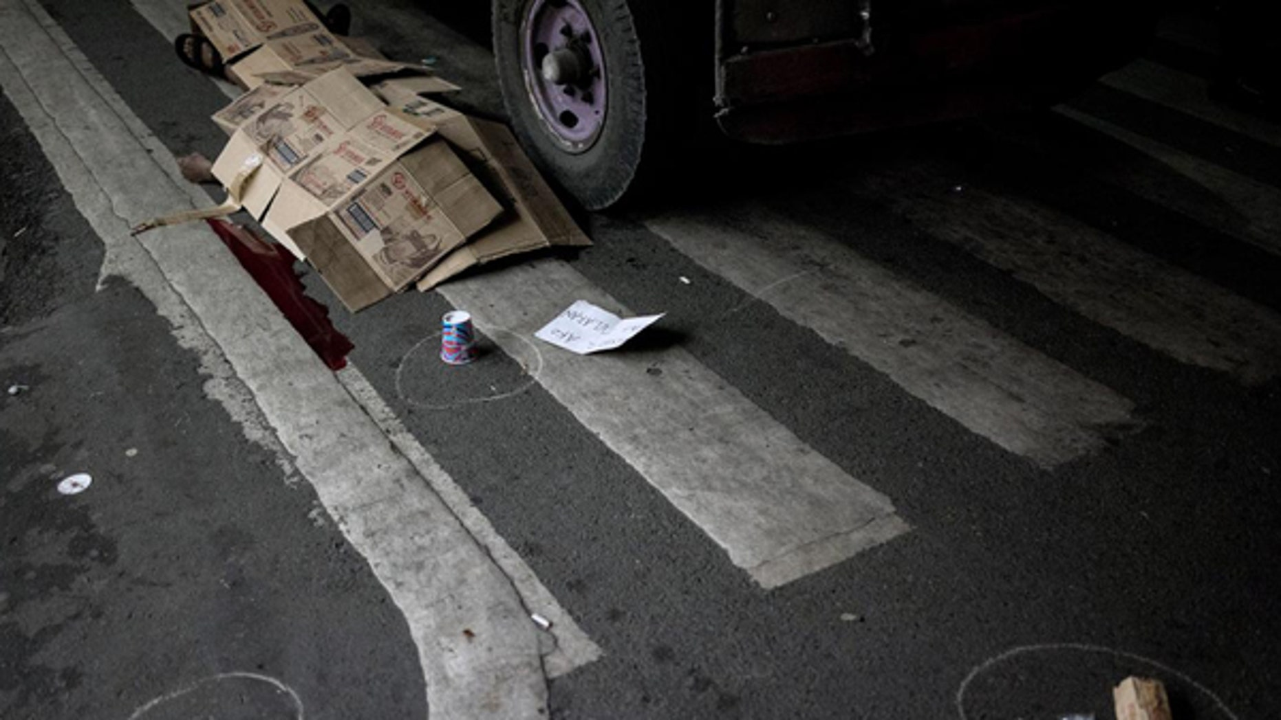 A man's body lies covered with cardboard boxes after he was shot dead by unidentified gunmen in front of a convenience store in Manila last October.