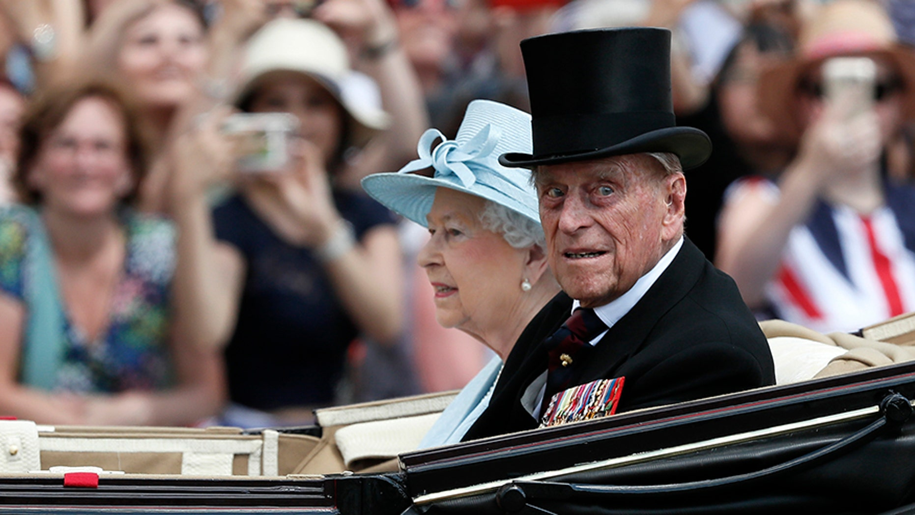 Britain's Queen Elizabeth II and Prince Philip return to Buckingham Palace in a carriage, after attending the annual Trooping the Color Ceremony, June 17, in London. Buckingham Palace said on Wednesday June 21, 2017, Prince Philip is good spirits after being admitted to hospital.