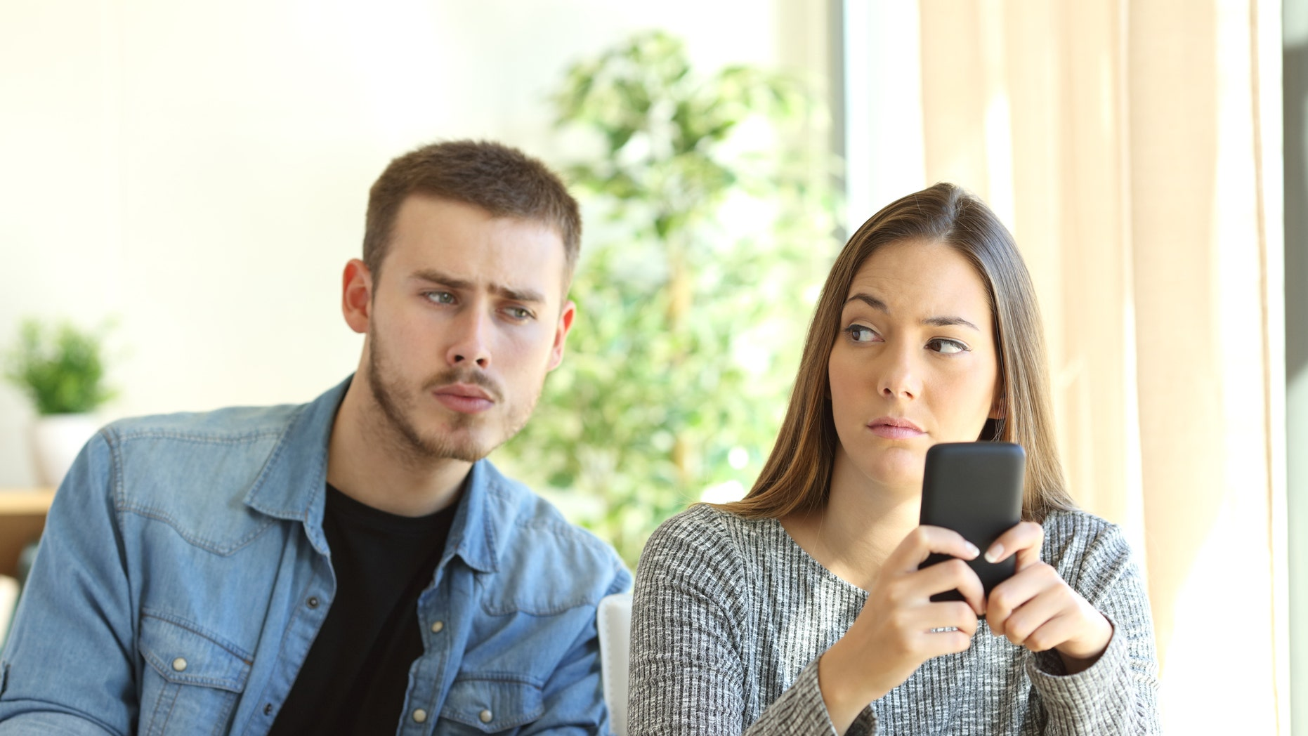 Jealous boyfriend spying his girlfriend watching her phone while she is looking him upset  (Credit: AntonioGuillem, iStock)