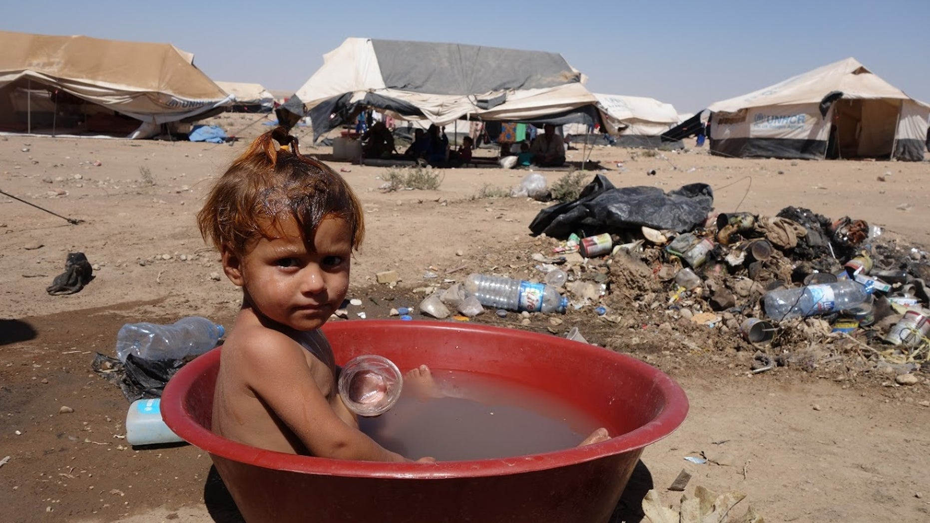 August, 2017: A child in a makeshift, polluted bath at Arisha camp in Hassakeh governorate, Syria. Around 6000 people are accommodated in the camp in very dire conditions, with no clean water, no medical services and no toilets. It was established in June 2017, and the area used to serve as an oil refinery, hence toxic waste could be found on site.